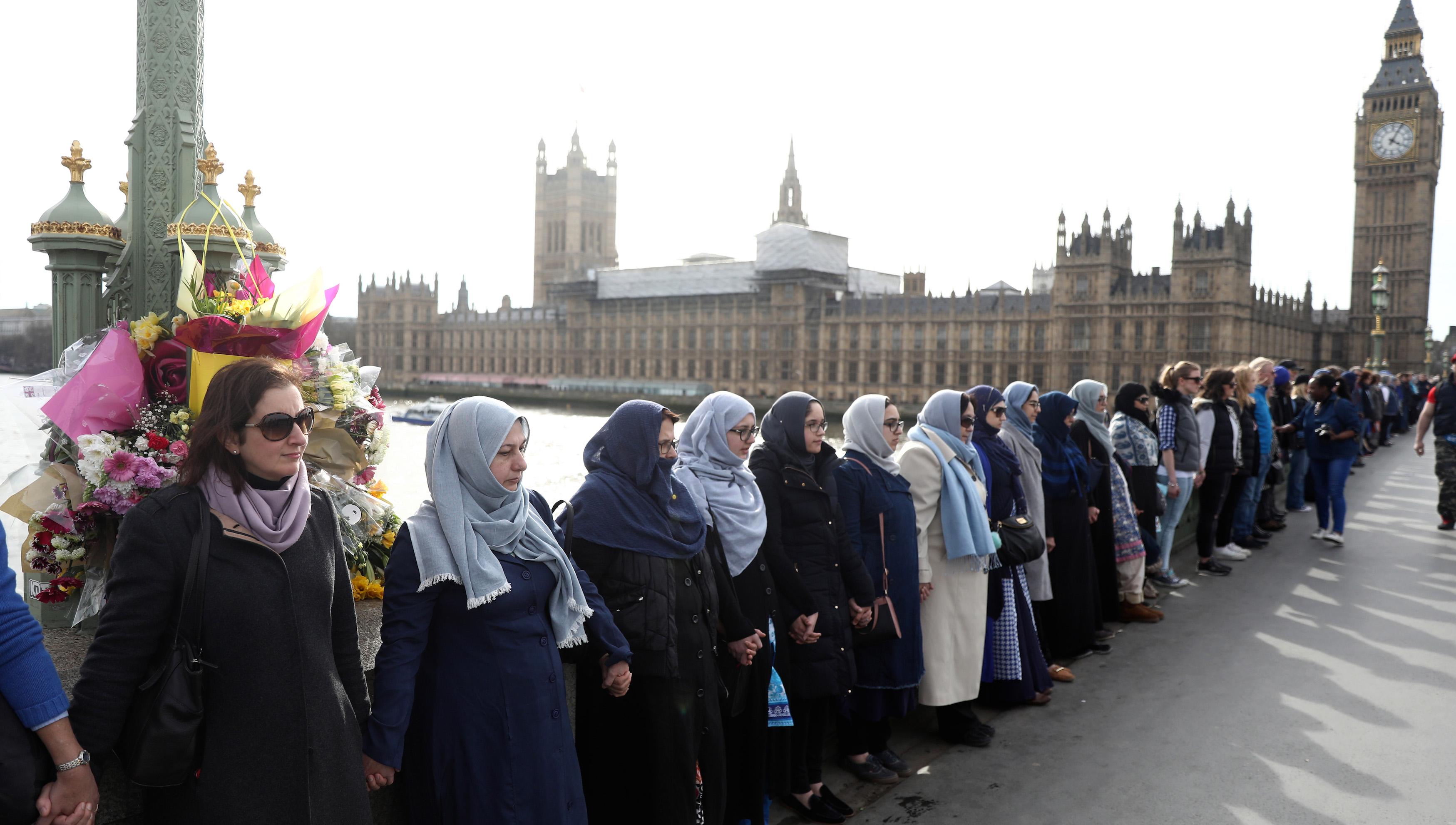 Participants in the Women's March, gather on Westminster Bridge to hold hands in silence, to remember victims of the attack in Westminster earlier in the week, in London, Britain March 26, 2017. REUTERS/Neil Hall - RTX32S55
