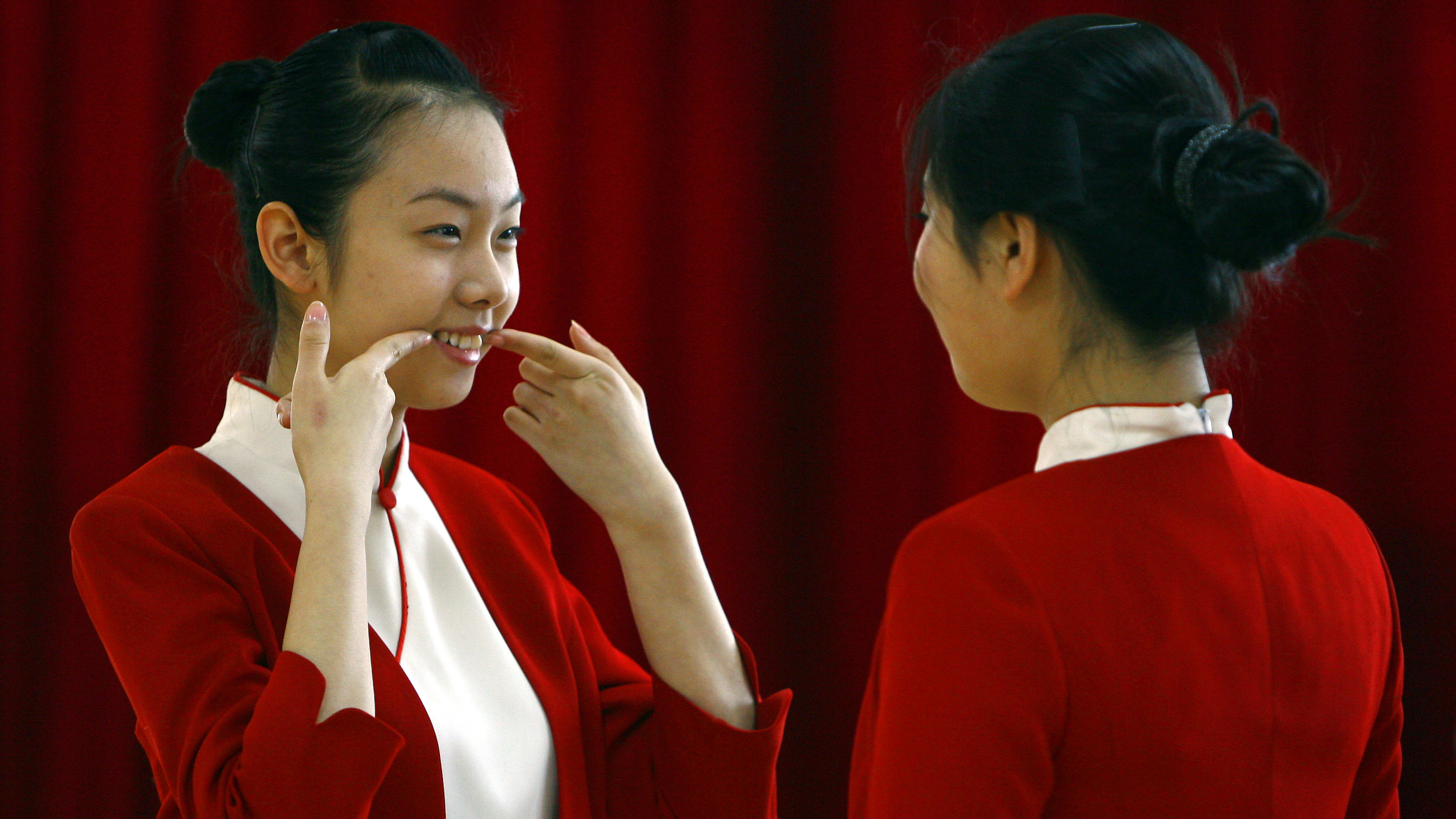 A student shows another how to smile during an etiquette training class at a vocational school in Beijing January 7, 2008.