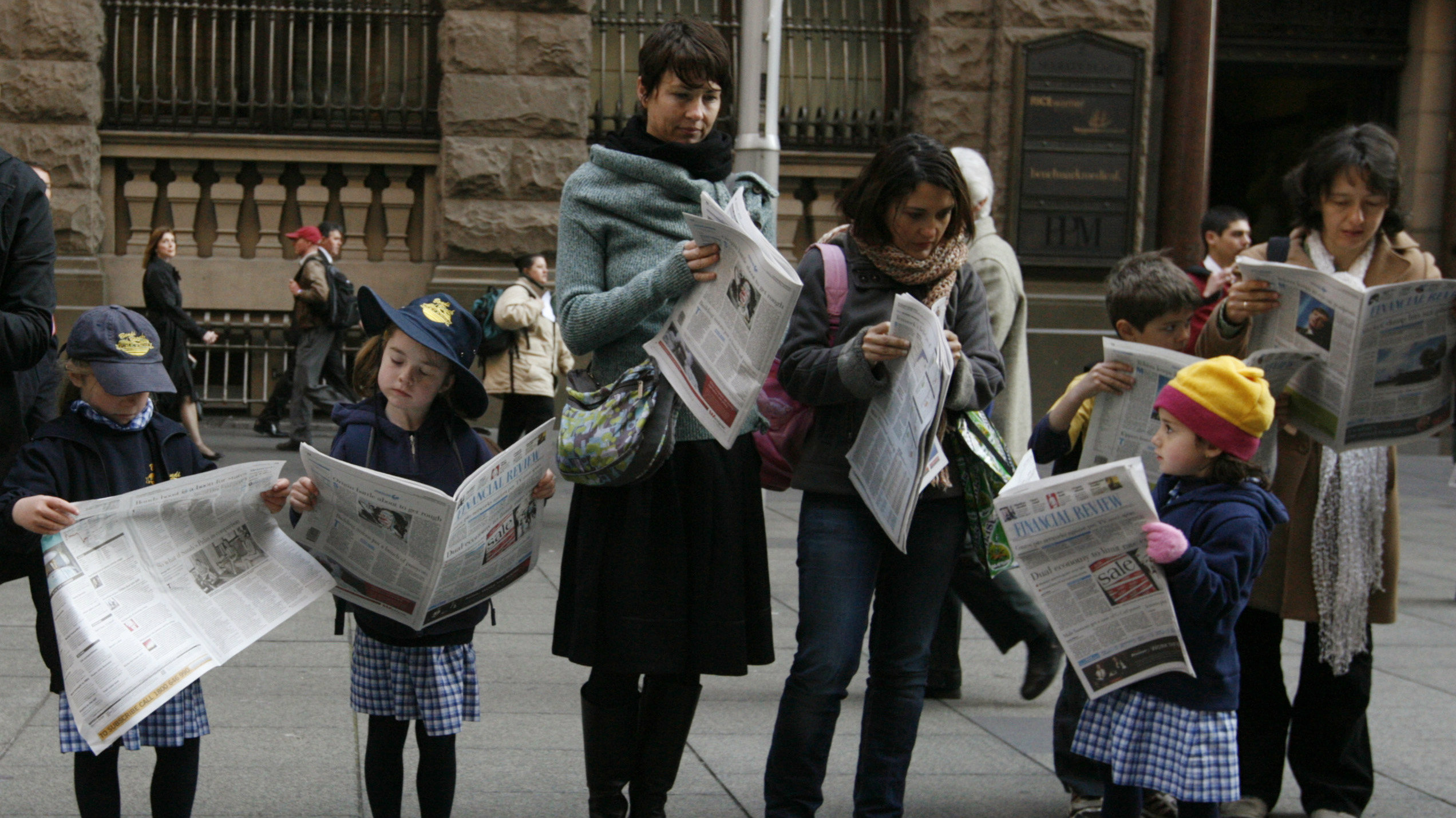 Children, mimicking the actions of their paired adult, read a newspaper at Martin Place in Central Sydney