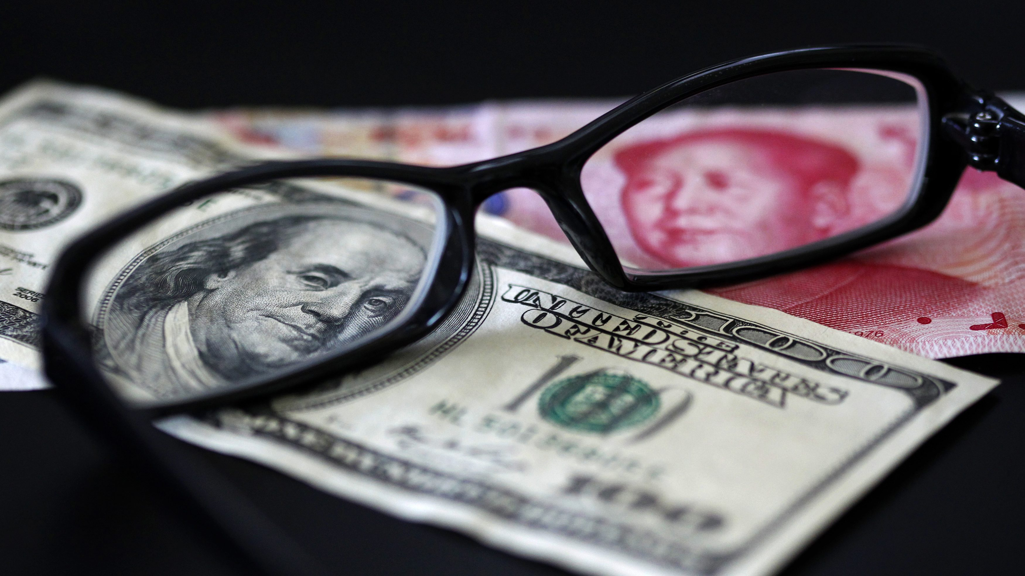 A U.S. dollar note (L) and a Chinese yuan banknote are seen through a pair of spectacles in this picture illustration taken in Taipei October 13, 2010. China's foreign exchange reserves soared in the third quarter and its trade surplus remained hefty, showing that the country is under both economic and political pressure to let the yuan rise more quickly.