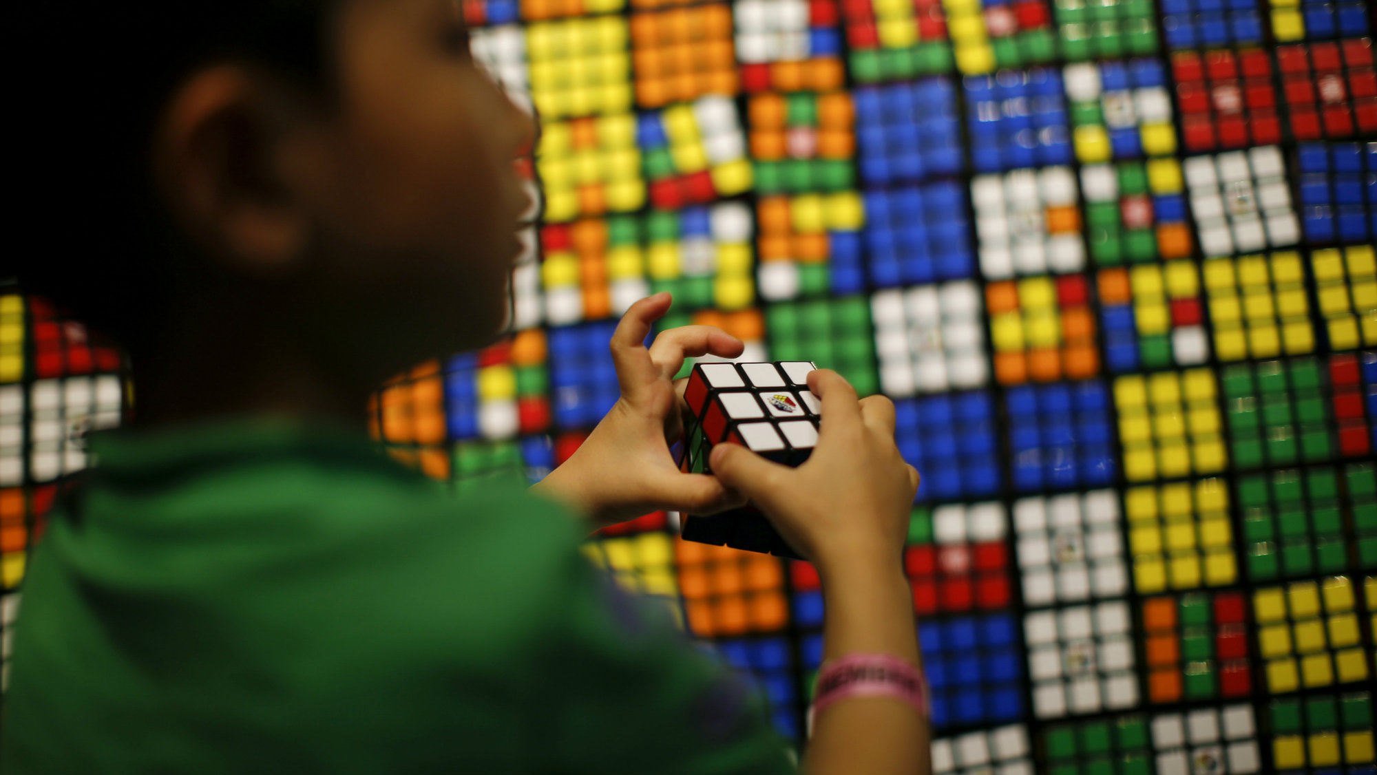 A boy plays with the Rubik's cube during an event to mark the 40th anniversary of the puzzle toy at the Liberty Science Center in Jersey City, New Jersey, April 26, 2014.