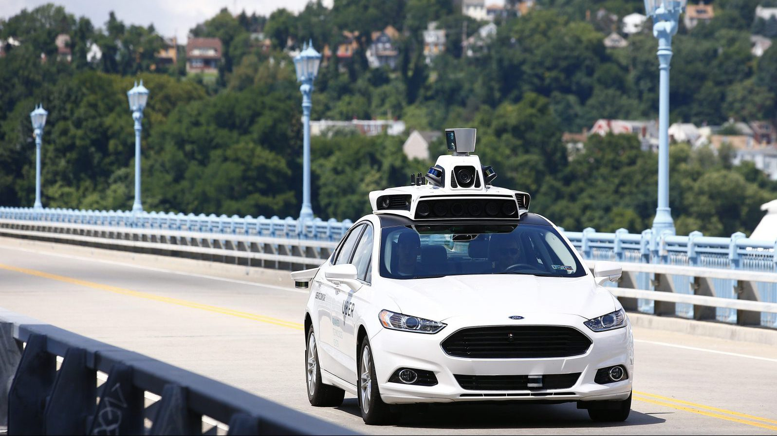 FILE - In this Thursday, Aug. 18, 2016, file photo, Uber employees test a self-driving Ford Fusion hybrid car, in Pittsburgh. After taking millions of factory jobs, robots could be coming for a new class of worker: people who drive for a living.