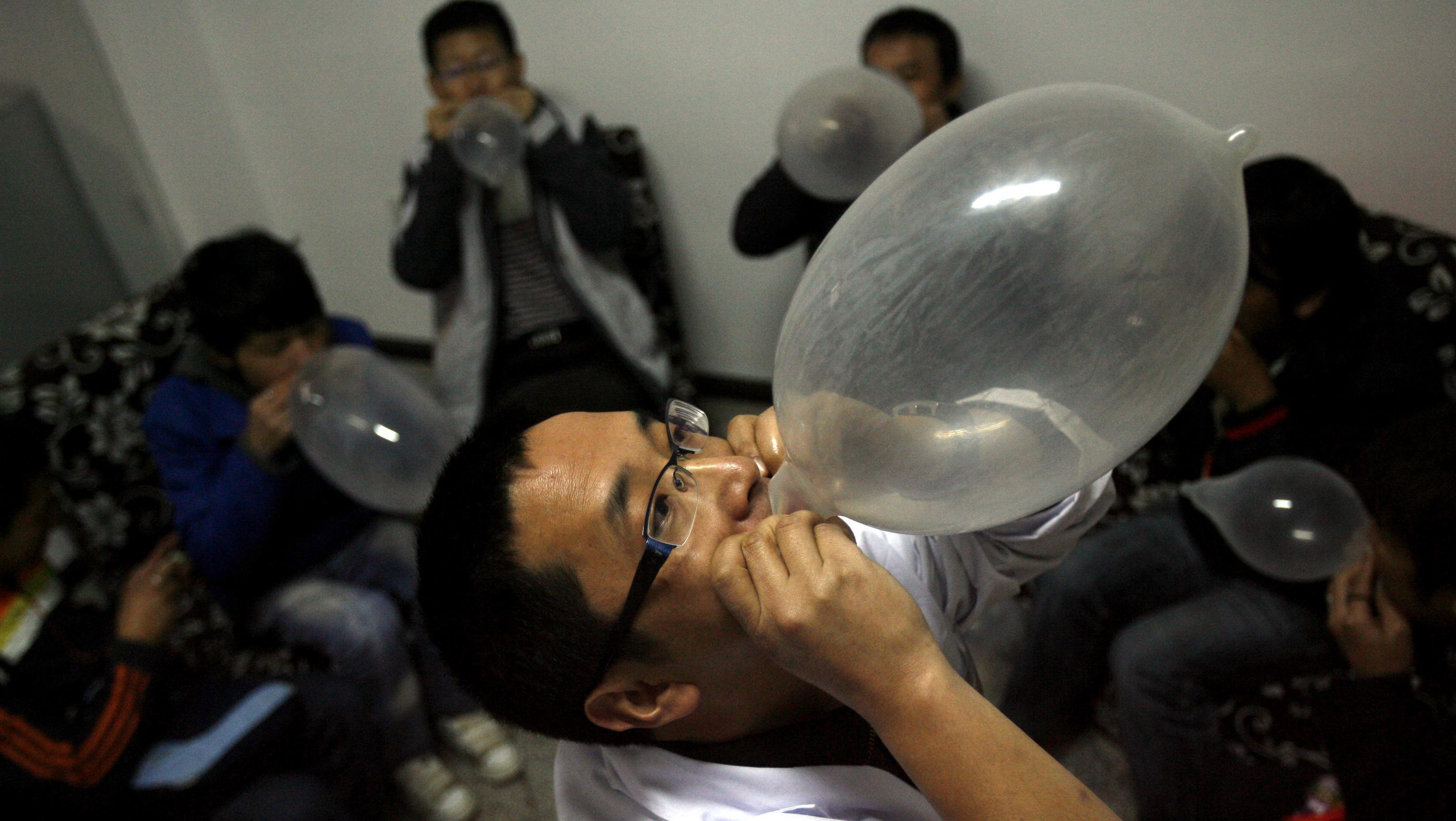 """Zhang Jianbo, a bar manager, blows up a condom as part of an event encouraging condom use by homosexuals in Dali, Yunnan province, November 26, 2009. Local authorities in southwestern Yunnan province are to convert the bar into a """"common room for partner education"""" for the gay community, as part of the official initiative to break social stigma against gay men, days after the health minister warned that homosexual sex has become a main factor in the spread of AIDS in the nation, Xinhua News Agency reported. Picture taken November 26, 2009. REUTERS/Stringer"""