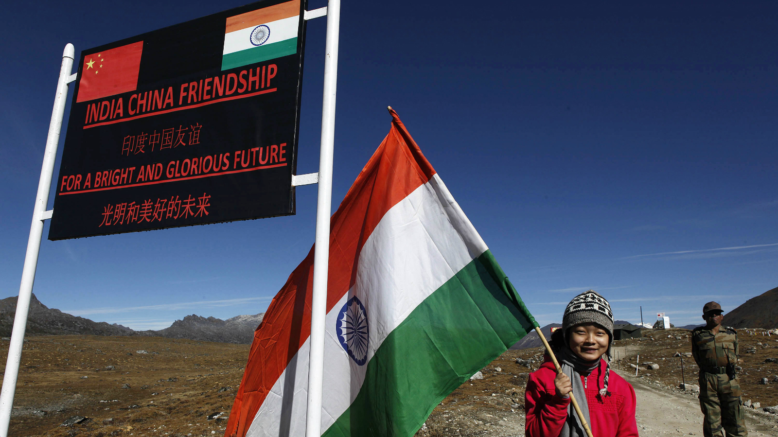 In this Oct. 21, 2012 file photo, an Indian girl poses for photographs with an Indian flag at the Indo China border in Bumla at an altitude of 15,700 feet (4,700 meters) above sea level in Arunachal Pradesh, India. While the recent troop standoff in a remote Himalayan desert spotlights a long-running border dispute between China and India, the two emerging giants are engaged in a rivalry for global influence that spreads much farther afield.