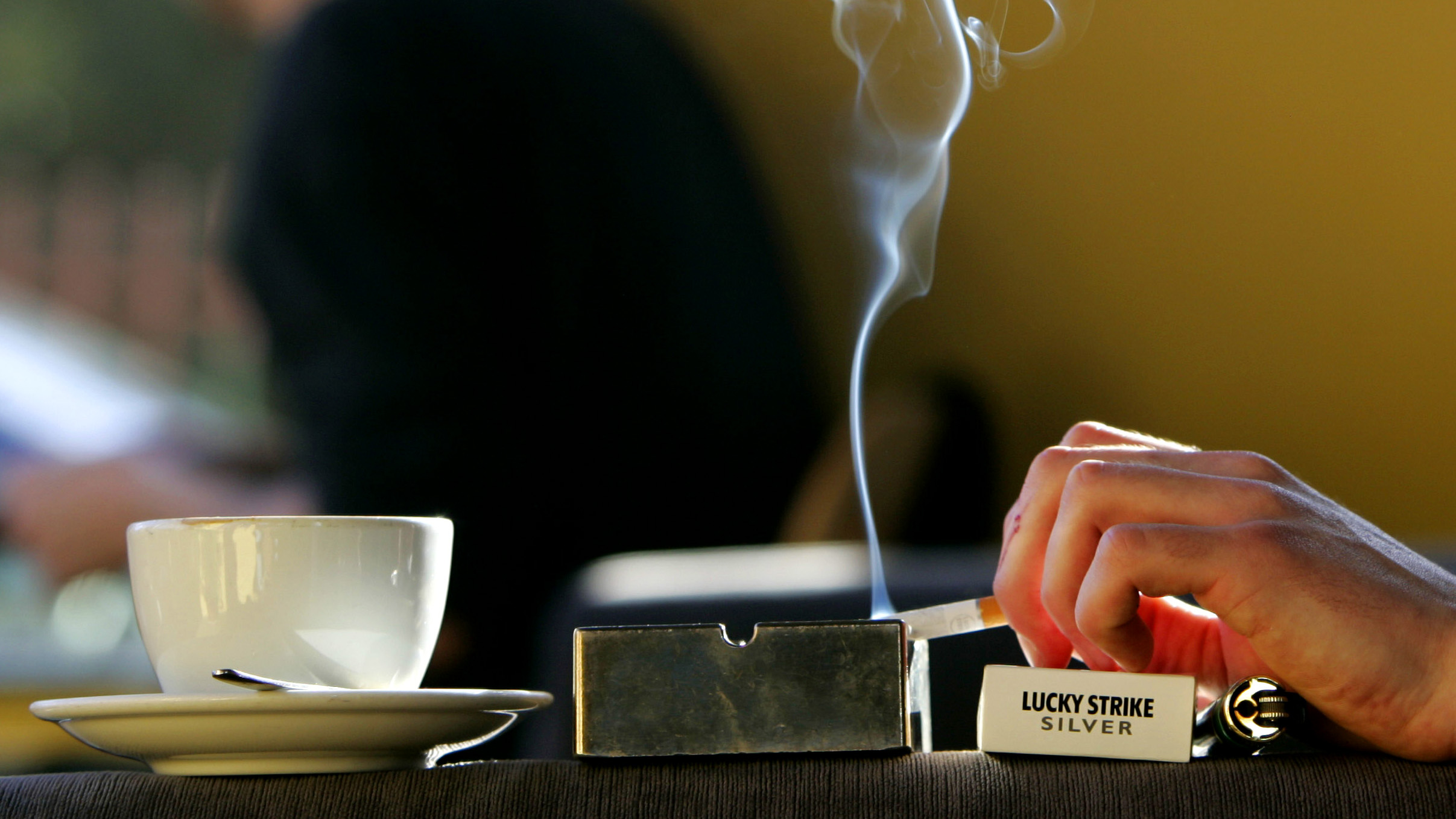 A customer smokes a cigarette in one of the last coffee shops in Glasgow to allow smoking, Scotland, November 10, 2004. Scotland is set to follow Ireland's pioneering anti-tobacco stance on Wednesday by announcing a ban on smoking in public buildings. - RTXN1J9