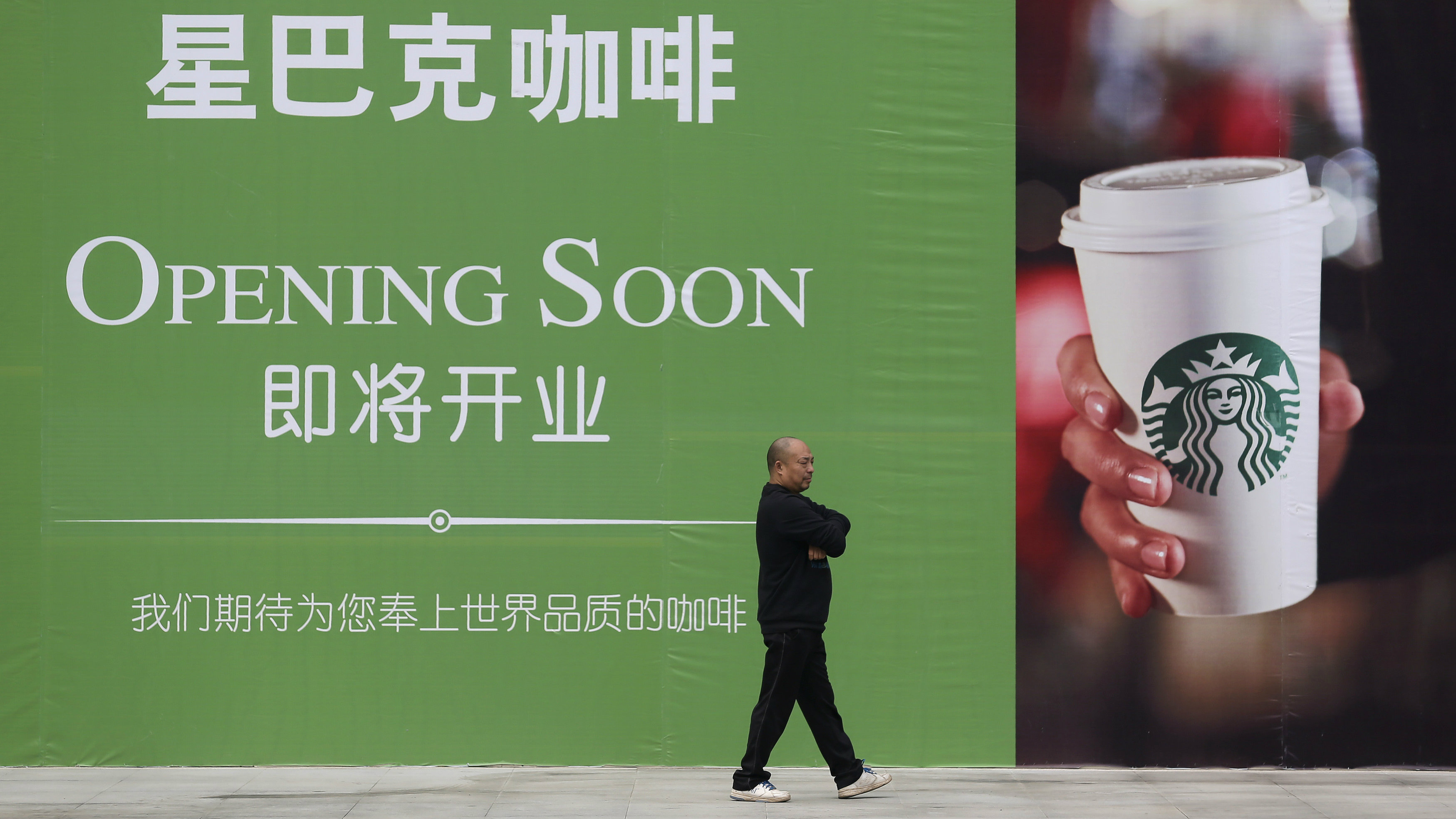 A man walks past an advertisement board of Starbucks in Wuhan, Hubei province, in this October 29, 2013 file photo. A China state television investigative report accusing Starbucks of overcharging local customers for coffee triggered enormous disquiet among journalists at the network and even some soul-searching after it aired. December 16, 2013