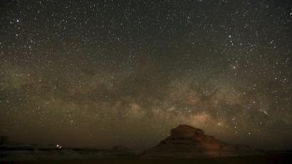 The stars in the Milky Way above a large rock.