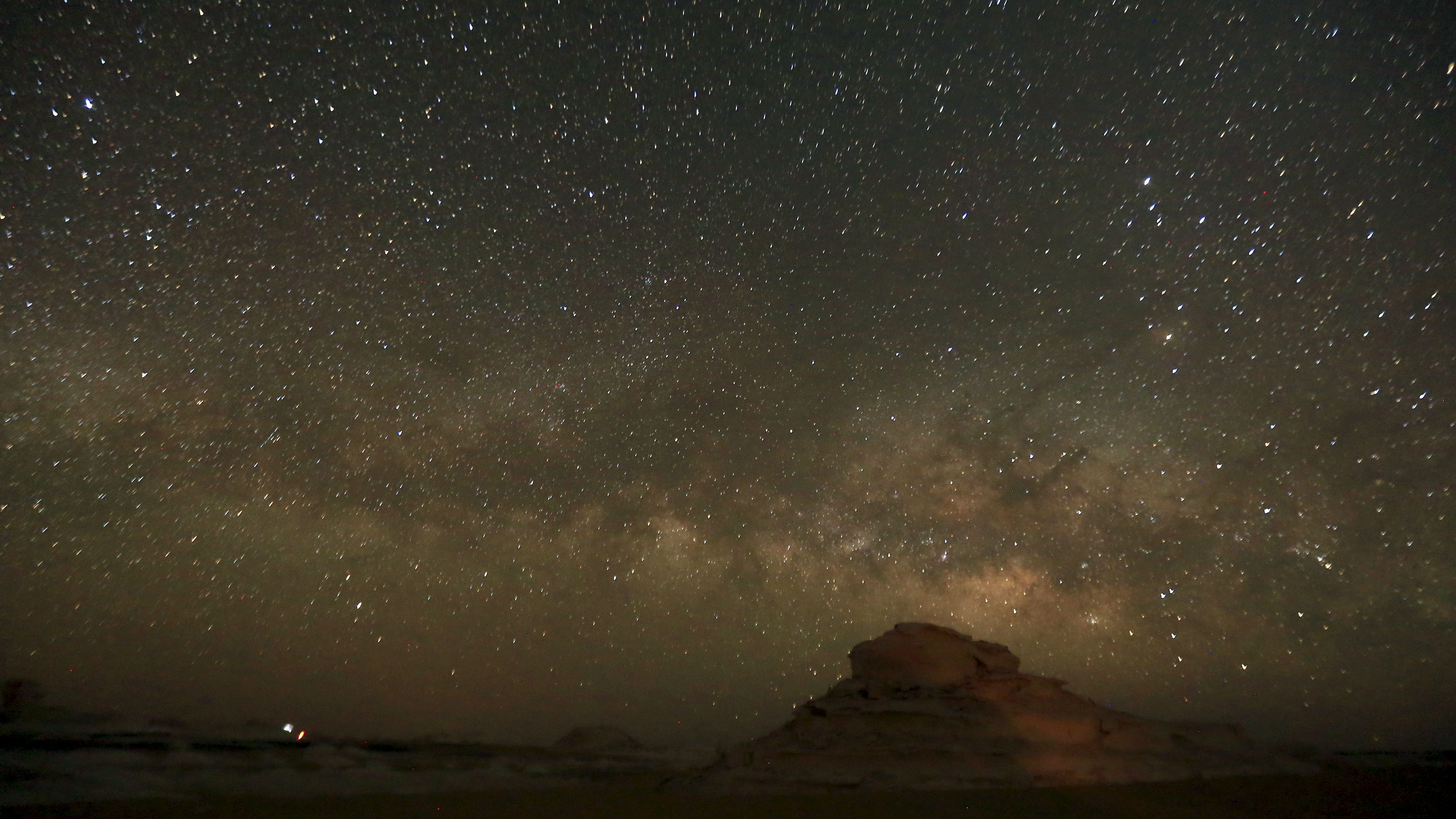 The 'Milky Way' is seen in the night sky over rocks in the White Desert north of the Farafra Oasis southwest of Cairo May 15, 2015. The White Desert, about 500 km southwest of the Egyptian capital Cairo, features limestone and chalk forms strangely shaped by the wind and sand, a terrain that gains in intensity when illuminated by the moon. Slightly to the north lies the Black Desert, given its name by the volcanic rock dolerite, similar to basalt. Four-by-four and trekking trips for tourists include Bedouin music around campfires and nights slept under a breathtaking array of stars. Picture taken May 15, 2015.