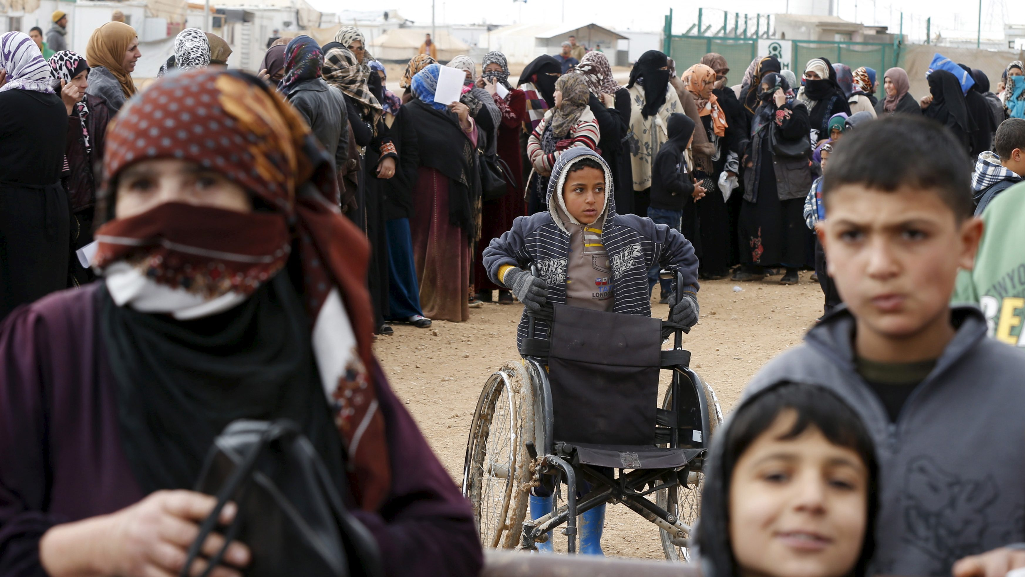 Syrian refugees stand in line at a refugee camp near the Jordanian border with Syria
