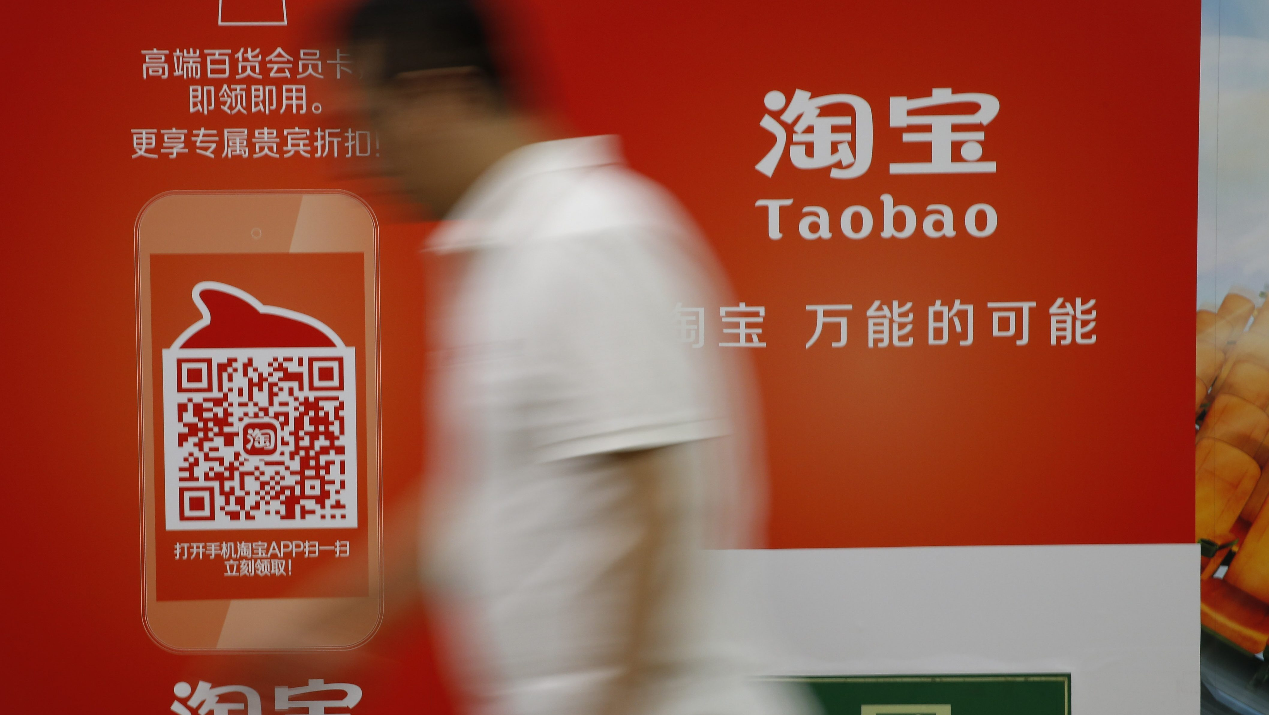 A man walks past an advertising billboard showing the mobile app of Alibaba's Taobao consumer-to-consumer site at a subway station in Beijing Thursday, Sept. 18, 2014. Alibaba Group's U.S. stock offering is a wakeup call about an emerging wave of technology giants in China's state-dominated economy.