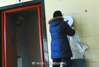 People pulling toilet papers in the restrooms at the Temple of Heaven Park in Beijing.