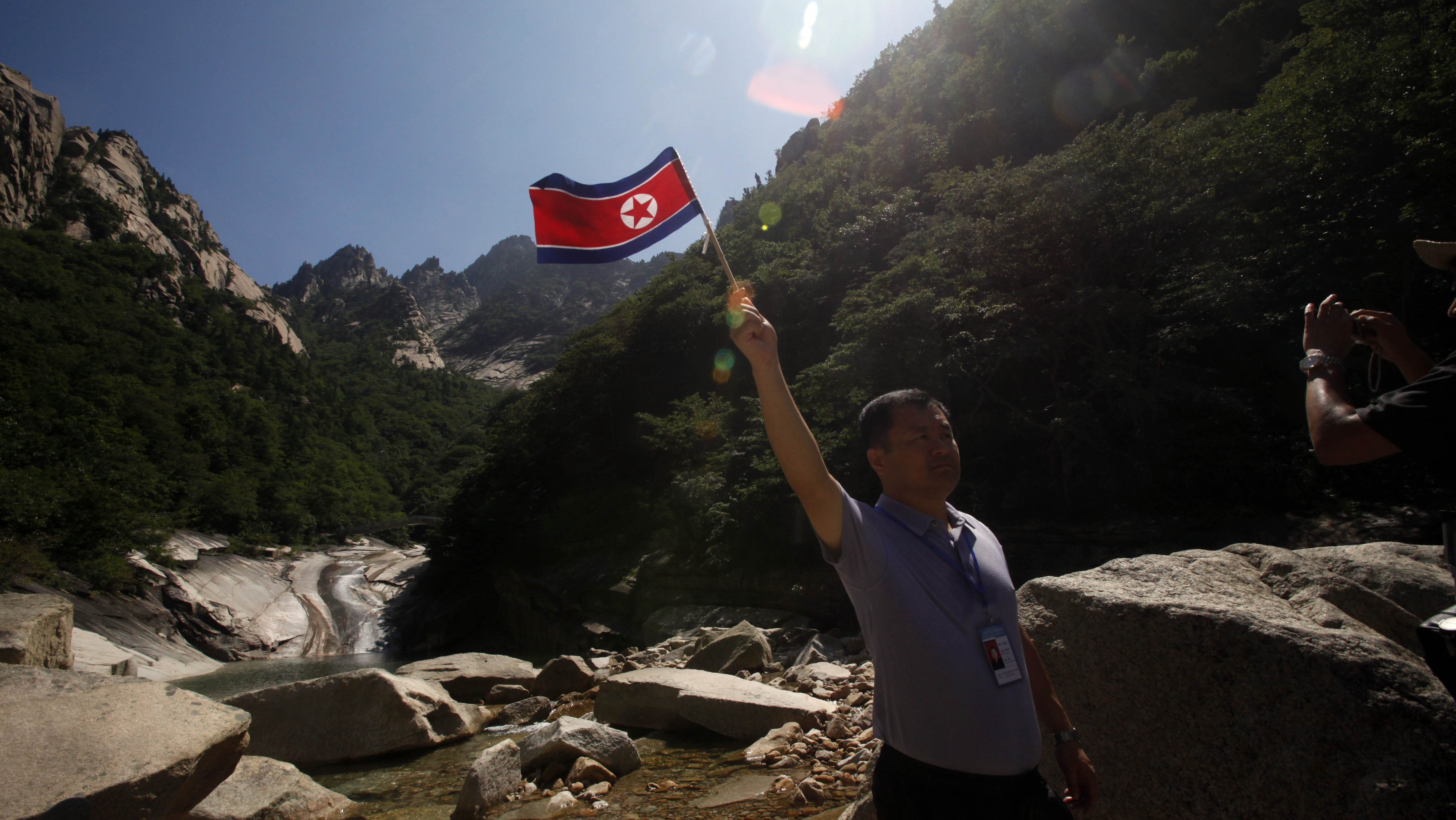 A Chinese tourist poses with a North Korean flag as he visits Mount Kumgang in North Korea, Wednesday, Aug. 31, 2011. Since South Korean tourists have been barred from the luxury resort, known abroad as Diamond Mountain, North Korea has begun courting Chinese and other international tourists. (AP Photo/Ng Han Guan)