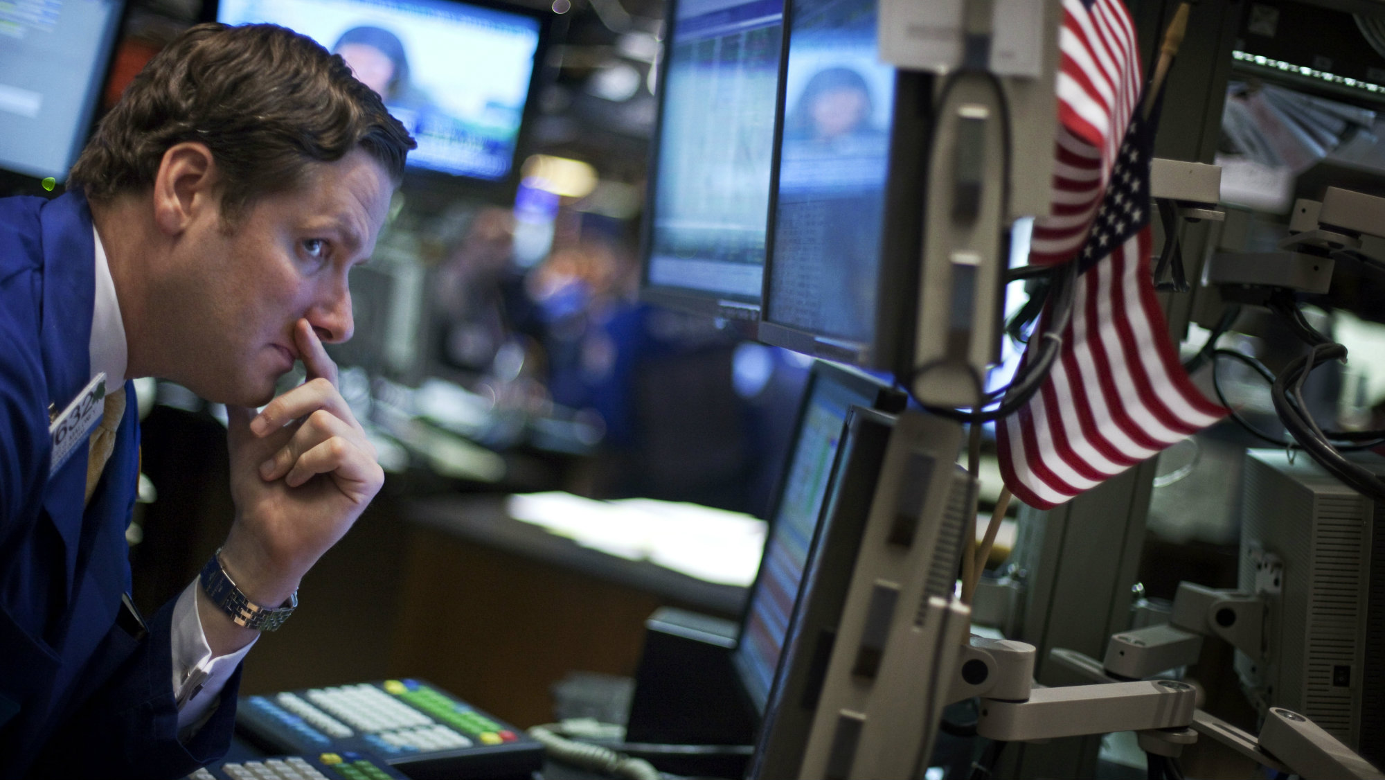 A trader looks at his screens while working on the floor of the New York Stock Exchange.