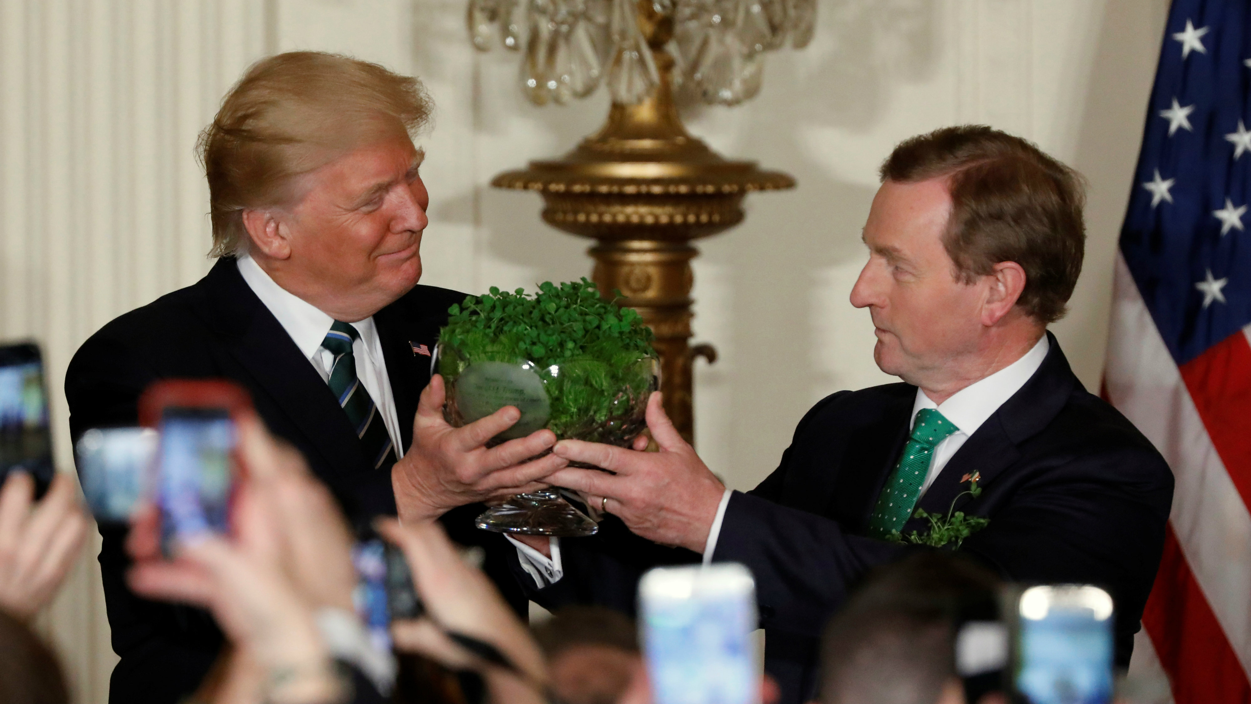 Ireland's Prime Minister Enda Kenny (R) presents a traditional gift of a bowl of shamrocks to U.S. President Donald Trump during a St. Patrick's Day reception at the White House in Washington, U.S. March 16, 2017.