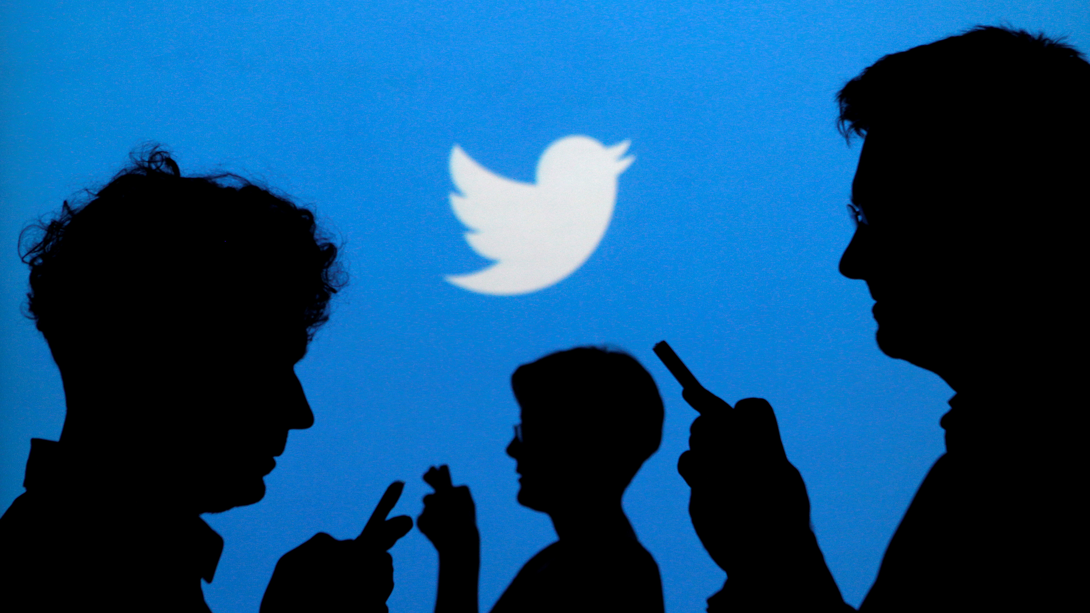 FILE PHOTO: People holding mobile phones are silhouetted against a backdrop projected with the Twitter logo in this illustration picture taken September 27, 2013. REUTERS/Kacper Pempel/Illustration/File Photo - RTX2Q1TA