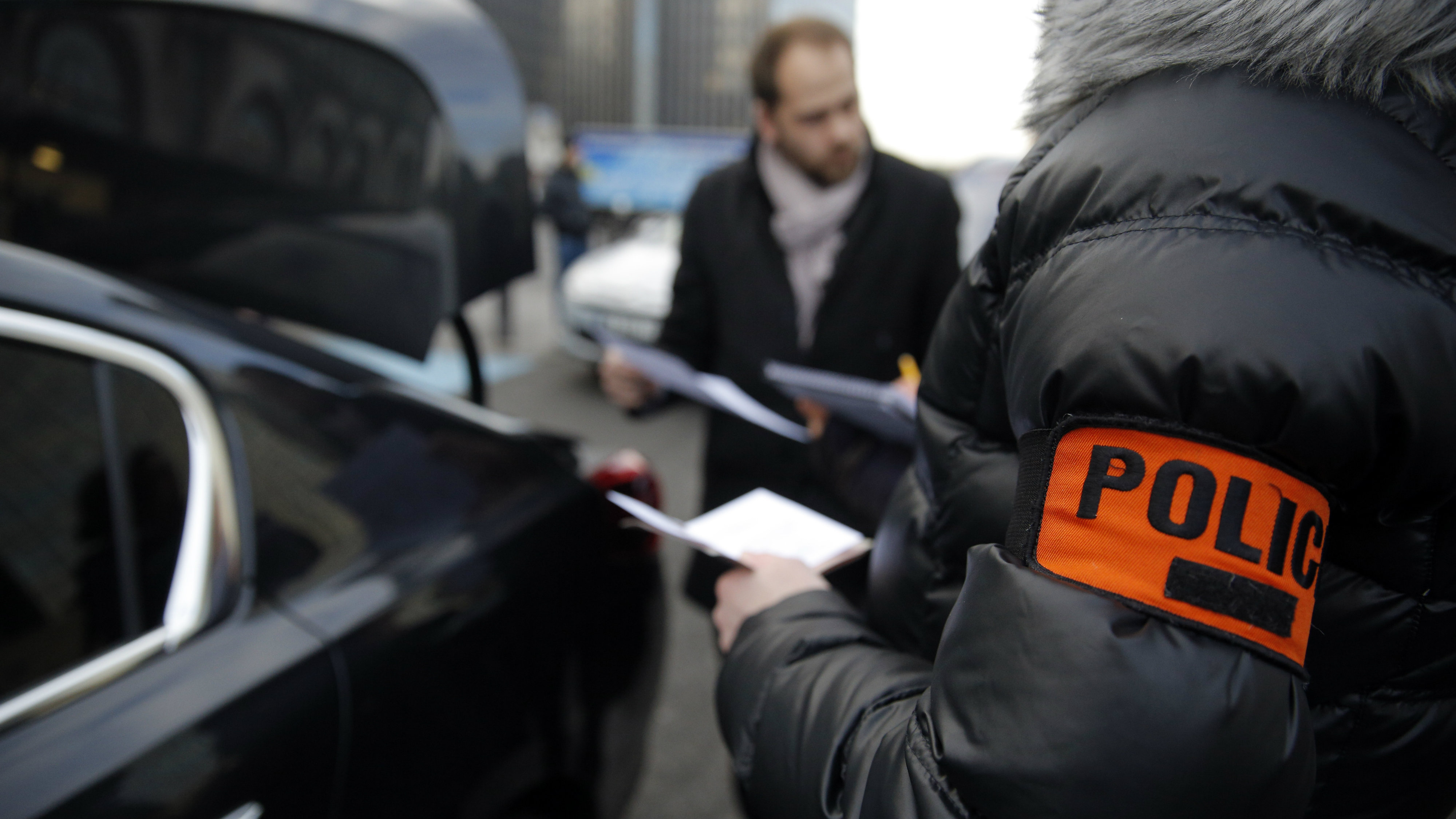 Plainclothes police officers check chauffeurs at the Paris' Gare de Lyon railway station, Thursday, Feb. 11, 2016. Chauffeurs claim they are victims of discrimination by the government, while taxi drivers complain for unfair competition from services such as Uber, during several protests in the recent weeks. (AP Photo/Christophe Ena)