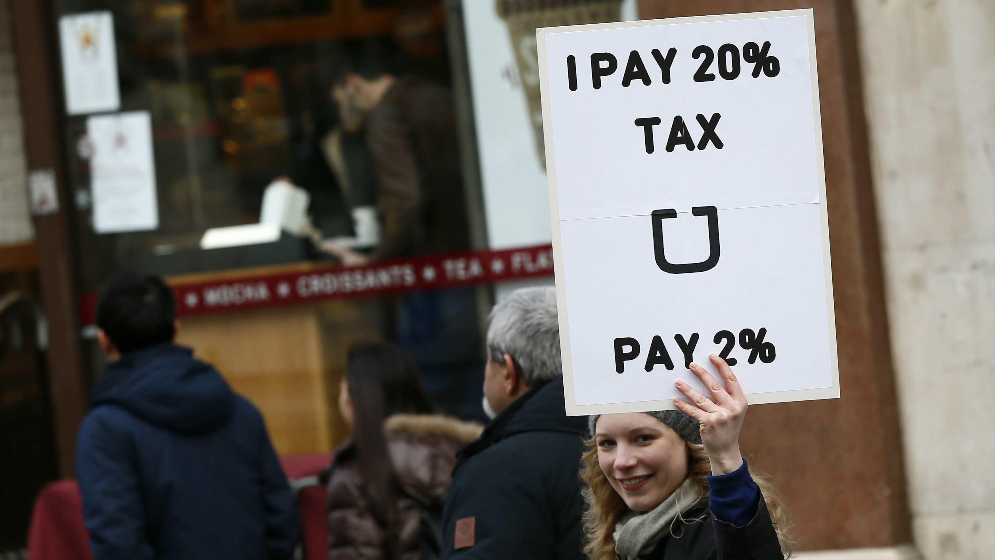 A protester holds up a placard in a protest by London cab drivers against Uber in central London, Britain February 10, 2016. REUTERS/Stefan Wermuth