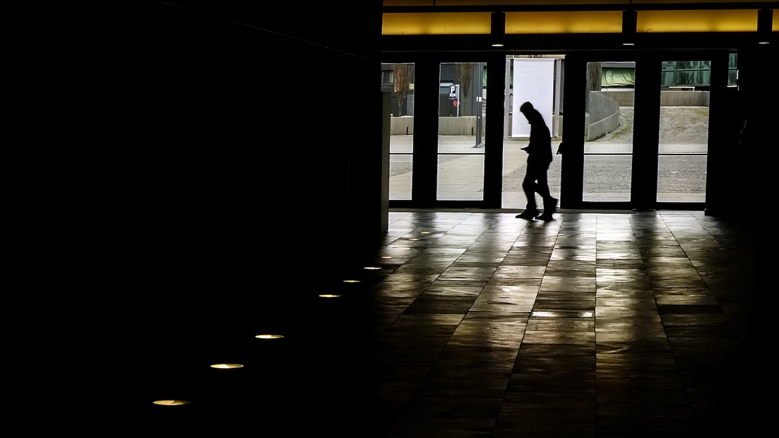 People walk past inside at a auditorium beside to a line of spotlights for the illumination of the place, in Pamplona, northern Spain, Monday, March 6, 2017. (AP Photo/Alvaro Barrientos)
