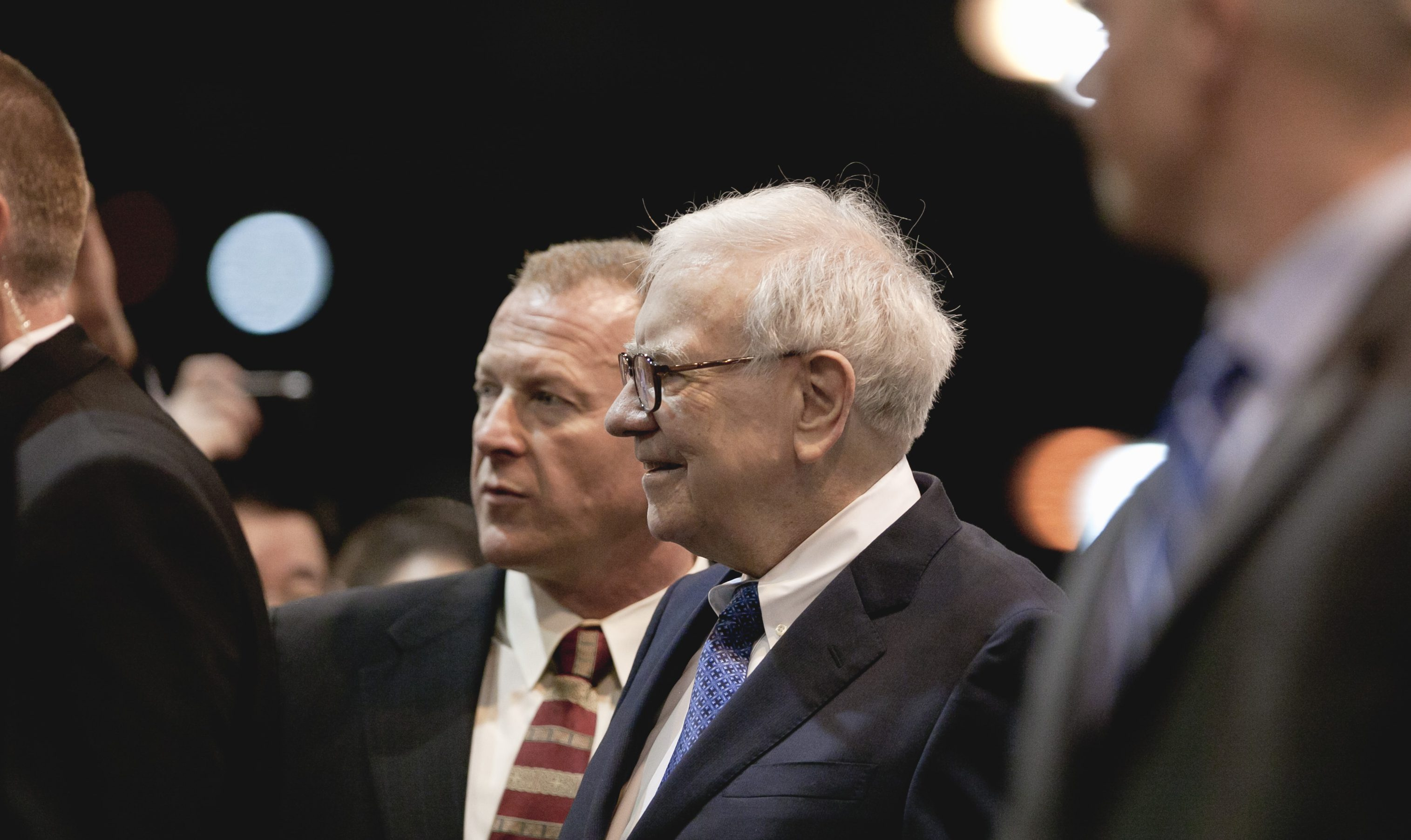 Warren Buffett, chairman and CEO of Berkshire Hathaway, center right, tours the exhibitor's floor with his chief of security Dan Clark, prior to holding the Berkshire Hathaway shareholders meeting in Omaha, Neb., Saturday, May 5, 2012. Berkshire Hathaway is holding it's annual shareholders meeting this weekend. (AP Photo/Nati Harnik)
