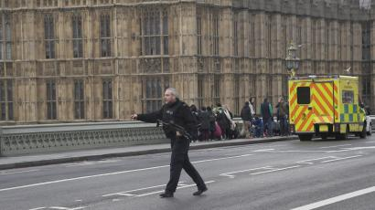 An armed police officer runs accross the road during an incident on Westminster Bridge in London