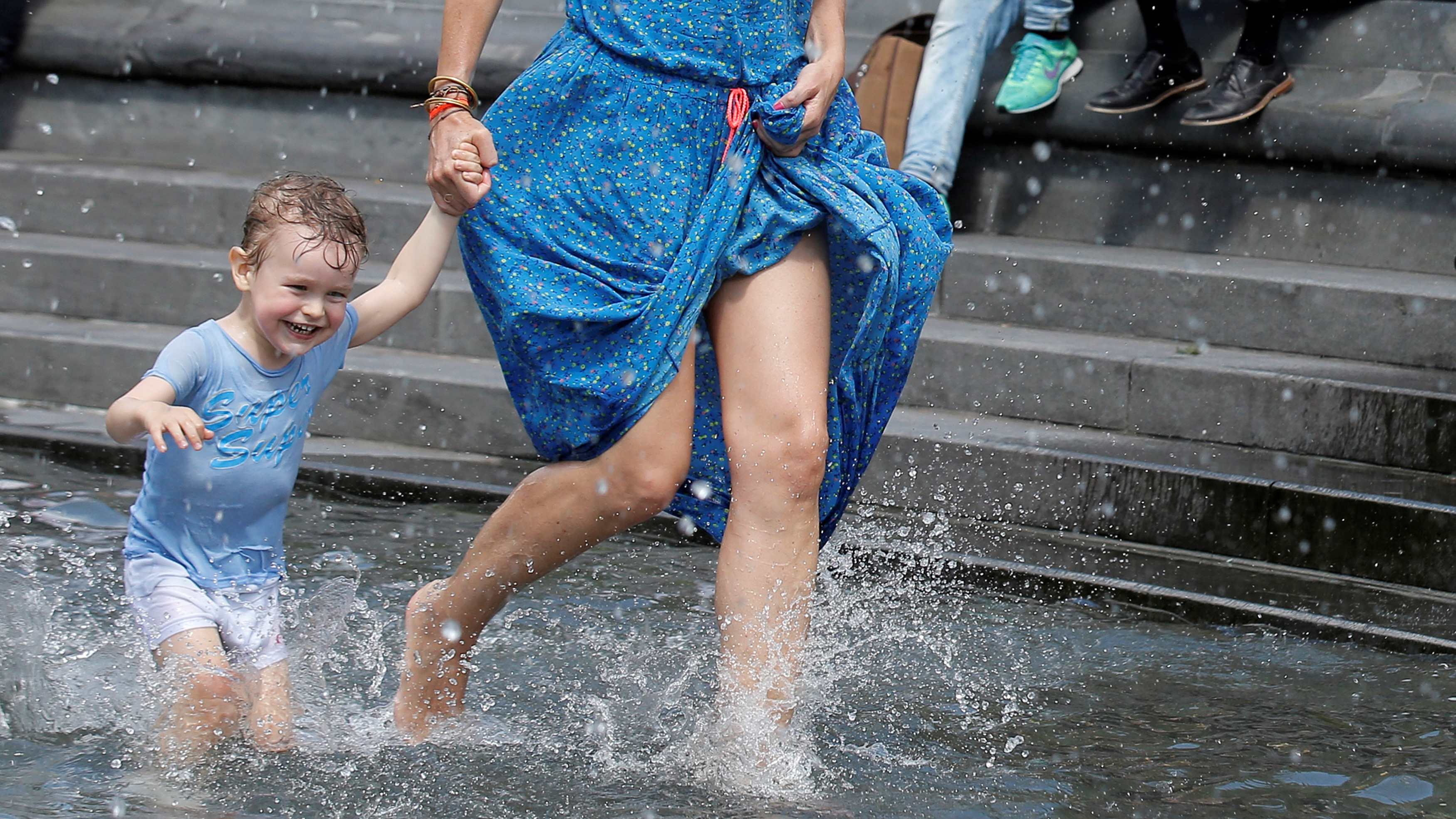 A woman plays with her child in a fountain.