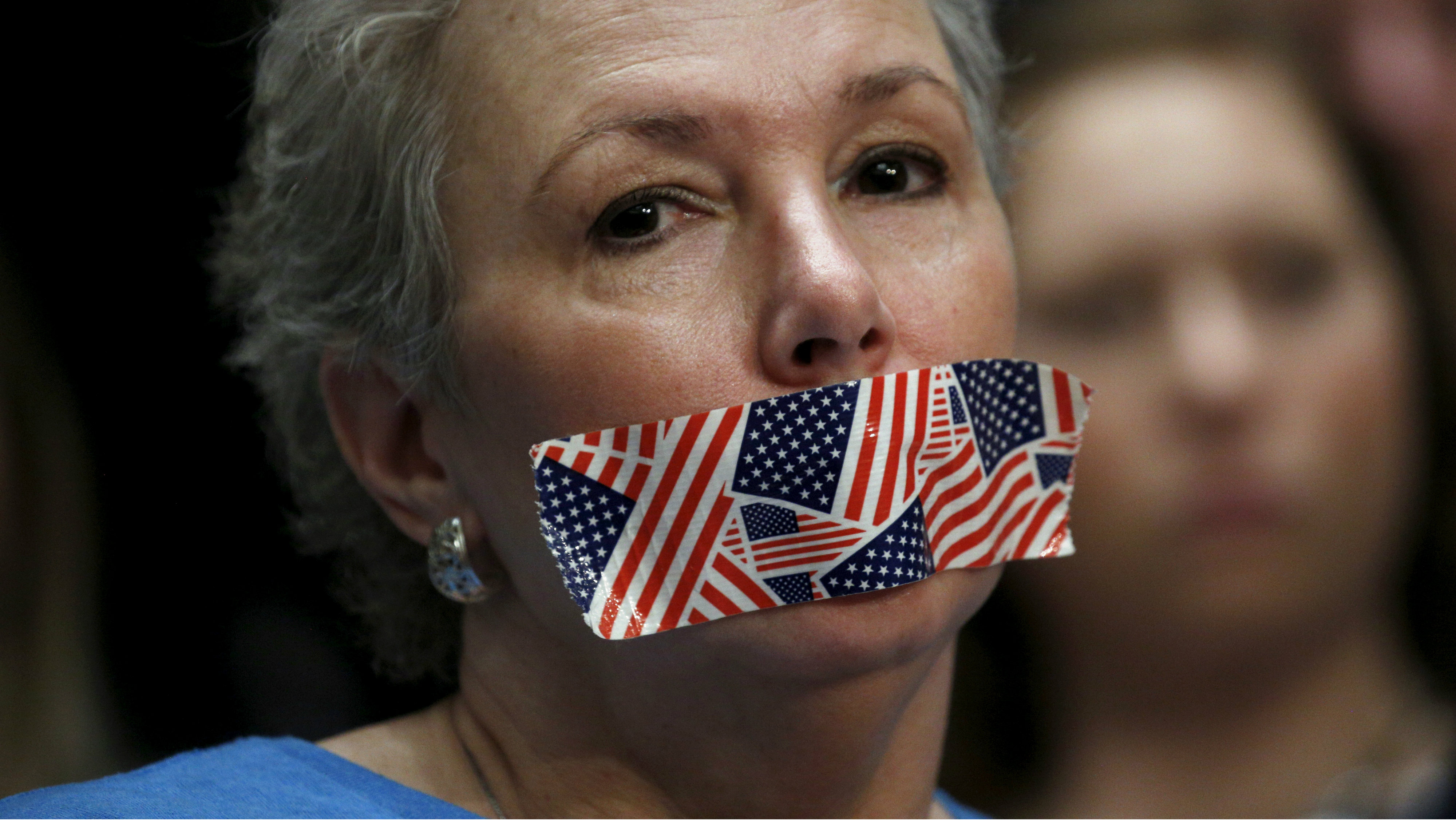 "A protester wears stars and stripes tape over her mouth during a House Appropriations hearing on ""World Wide Threats"" on Capitol Hill in Washington February 25, 2016. The hearing featured testimony from heads of the CIA, FBI, NSA and DIA. REUTERS/Kevin Lamarque"