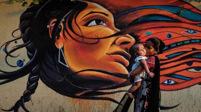 A mother kisses her child as she walks past graffiti in Mumbai