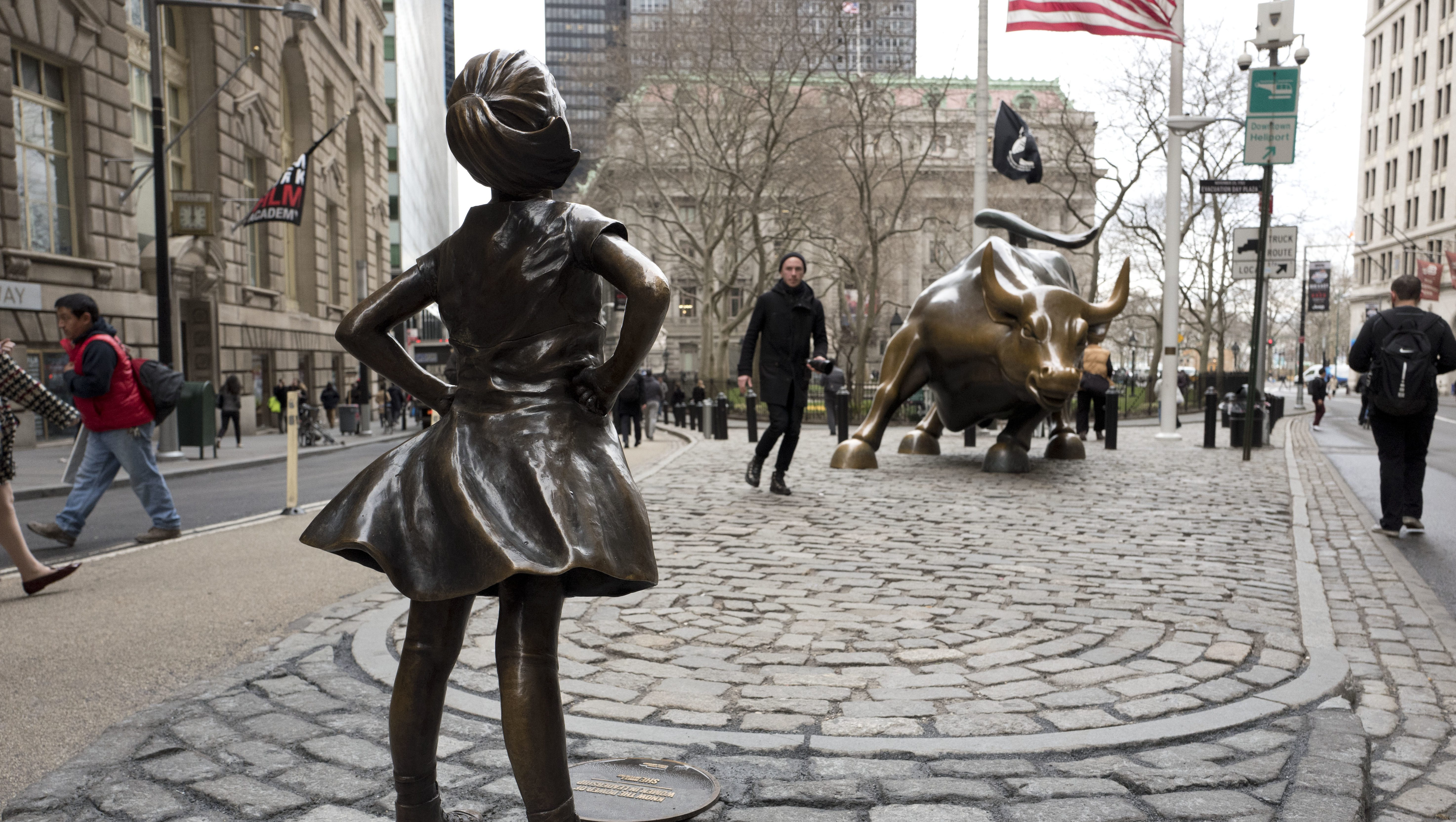 "A statue titled ""Fearless Girl"" faces the Wall Street bull, Wednesday, March 8, 2017, in New York.   A big investment firm, State Street Global Advisors, put the statue there to highlight International Women's Day.  The work by artist Kristen Visbal."