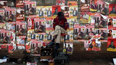 A man looks at campaign posters as he waits to cast his ballot, during the Jubilee Party primary elections, outside a polling centre in Nairob