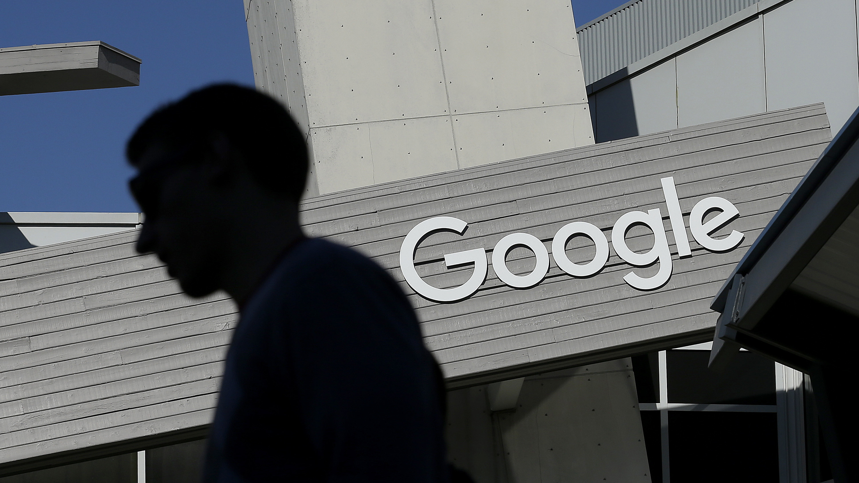 FILE - In this Nov. 12, 2015, file photo, a man walks past a building on the Google campus in Mountain View, Calif. Google and LinkedIn said July 13, 2016, that they have completed a massive land swap involving several Silicon Valley properties. (AP Photo/Jeff Chiu, File)