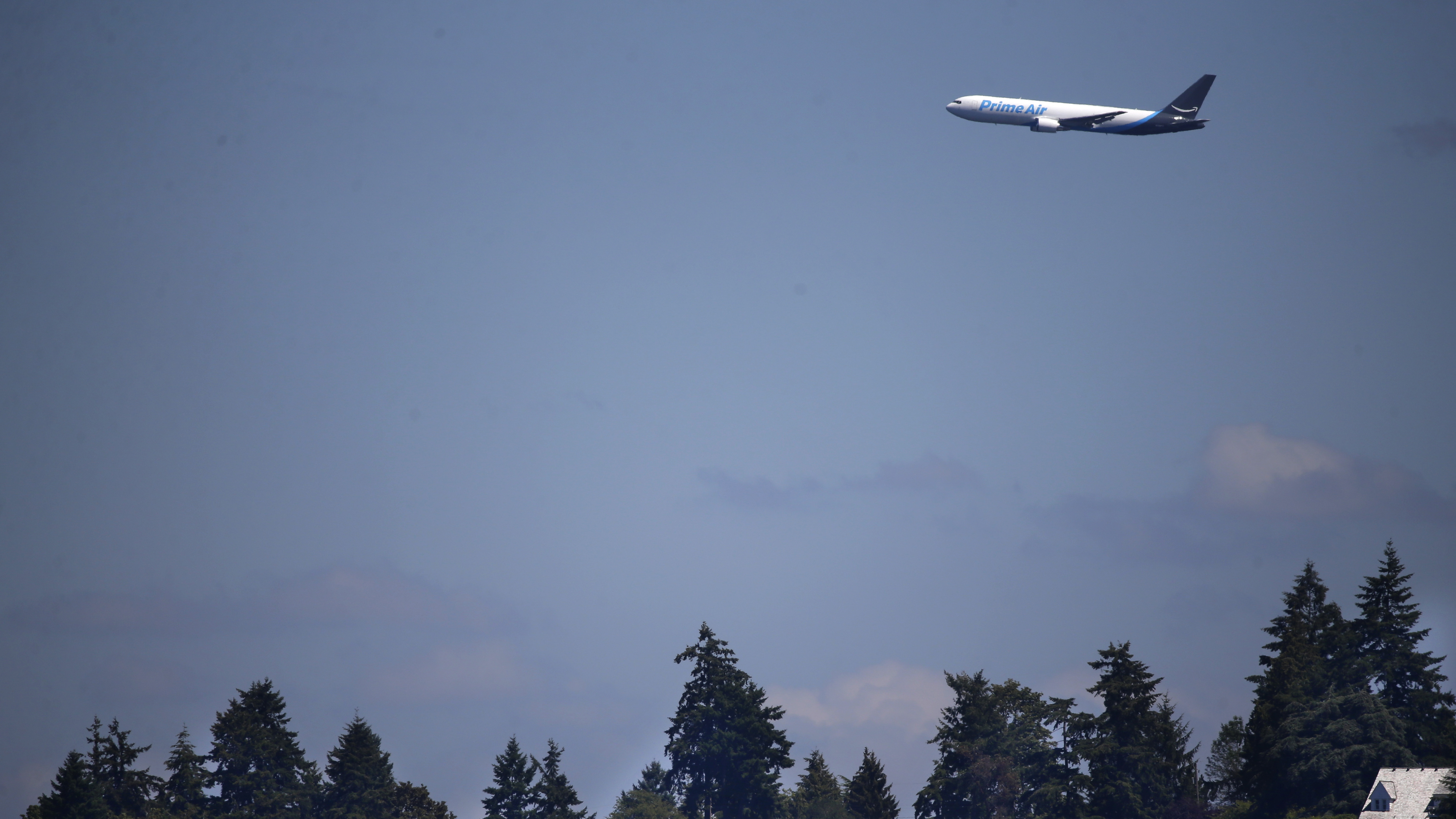 "A Boeing 767 with an Amazon.com ""Prime Air"" livery flies over houses on Lake Washington, Friday, Aug. 5, 2016, as part of the Boeing Seafair Air Show. Amazon unveiled its first branded cargo plane Thursday, one of 40 freighters that will make up the company's own air transportation network of 40 Boeing jets leased from Atlas Air and Air Transportation Services Group, which will operate the air cargo network. (AP Photo/Ted S. Warren)"