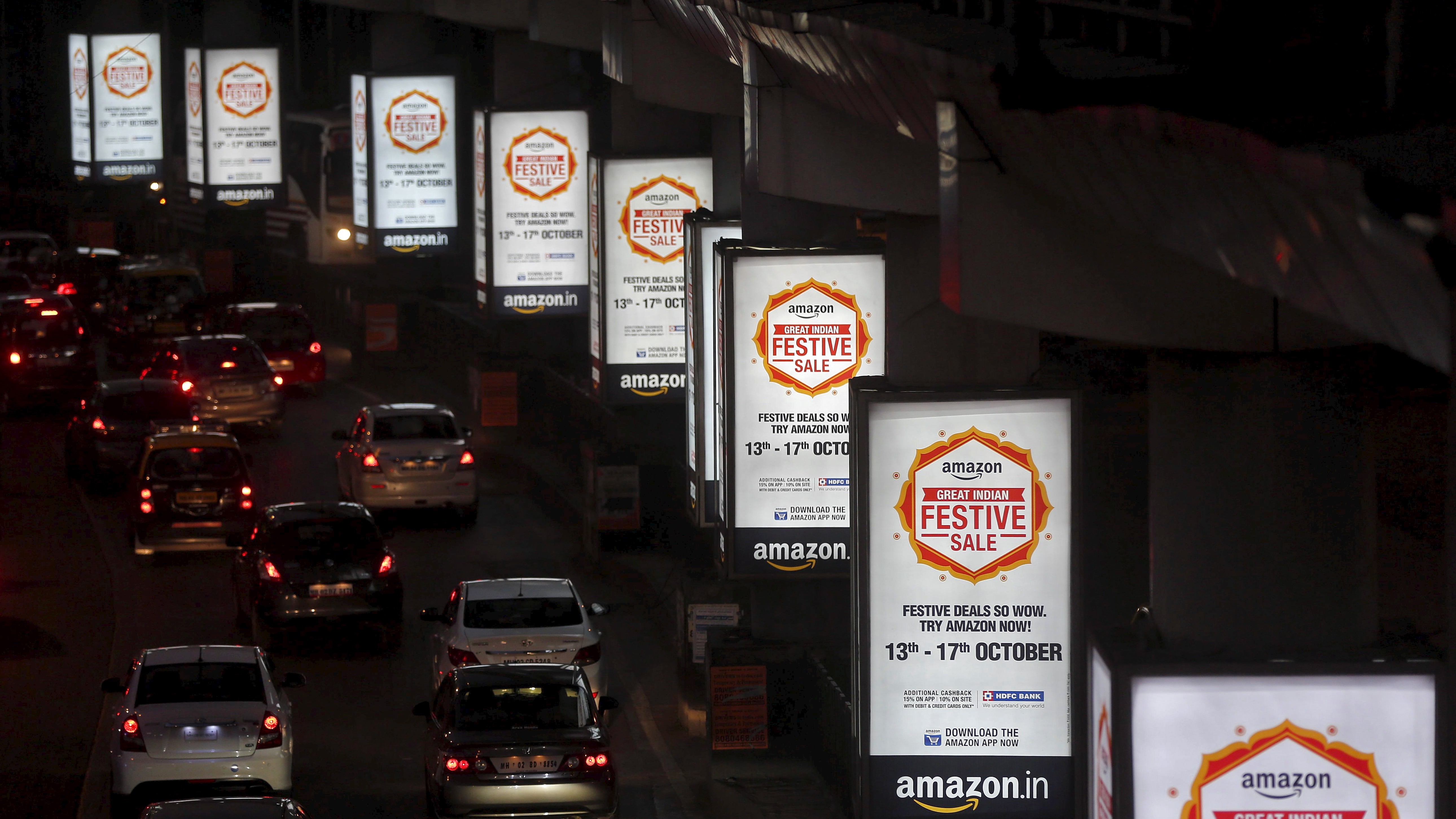Traffic moves on a road past advertisements of Indian online marketplace Amazon, in Mumbai, India, October 15, 2015. Amazon.com could emerge as the biggest winner from one of India's most important festive - and shopping - seasons that began this week, after the e-tailer offered steep discounts, swift delivery and even gold bars to grab market share. The month-long festive season culminates around November 10 in Diwali, or the Festival of Lights, but the first nine days are considered an especially auspicious time to make big purchases. Picture taken October 15, 2015.   REUTERS/Shailesh Andrade - RTS4PFR
