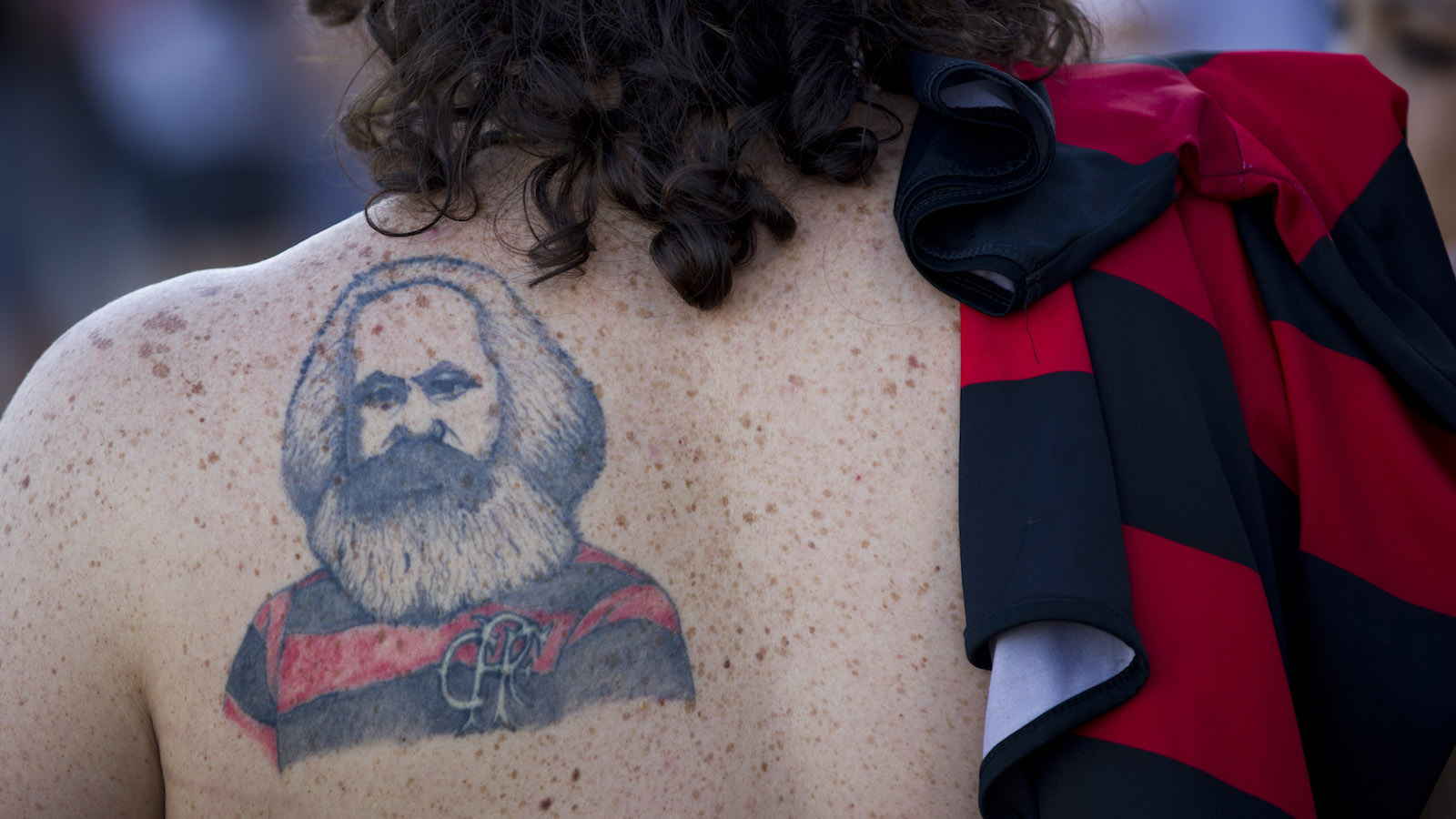 A protestor wearing a tattoo of Socialist philosopher Karl Marx with a jersey of the Flamengo soccer team marches during a demonstration against the privatization of the Maracana soccer stadium in Rio de Janeiro, Brazil, Sunday, June 3, 2012. The Maracana stadium will host the finals of both the 2013 Confederations Cup and the 2014 World Cup. (AP Photo/Victor R. Caivano)