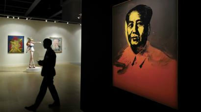 """A man walks past a painting """"Mao"""" by U.S. pop artist Andy Warhol during a media preview for the Sotheby's Modern and Contemporary Art Evening Sale in Hong Kong, Friday, March 31, 2017."""