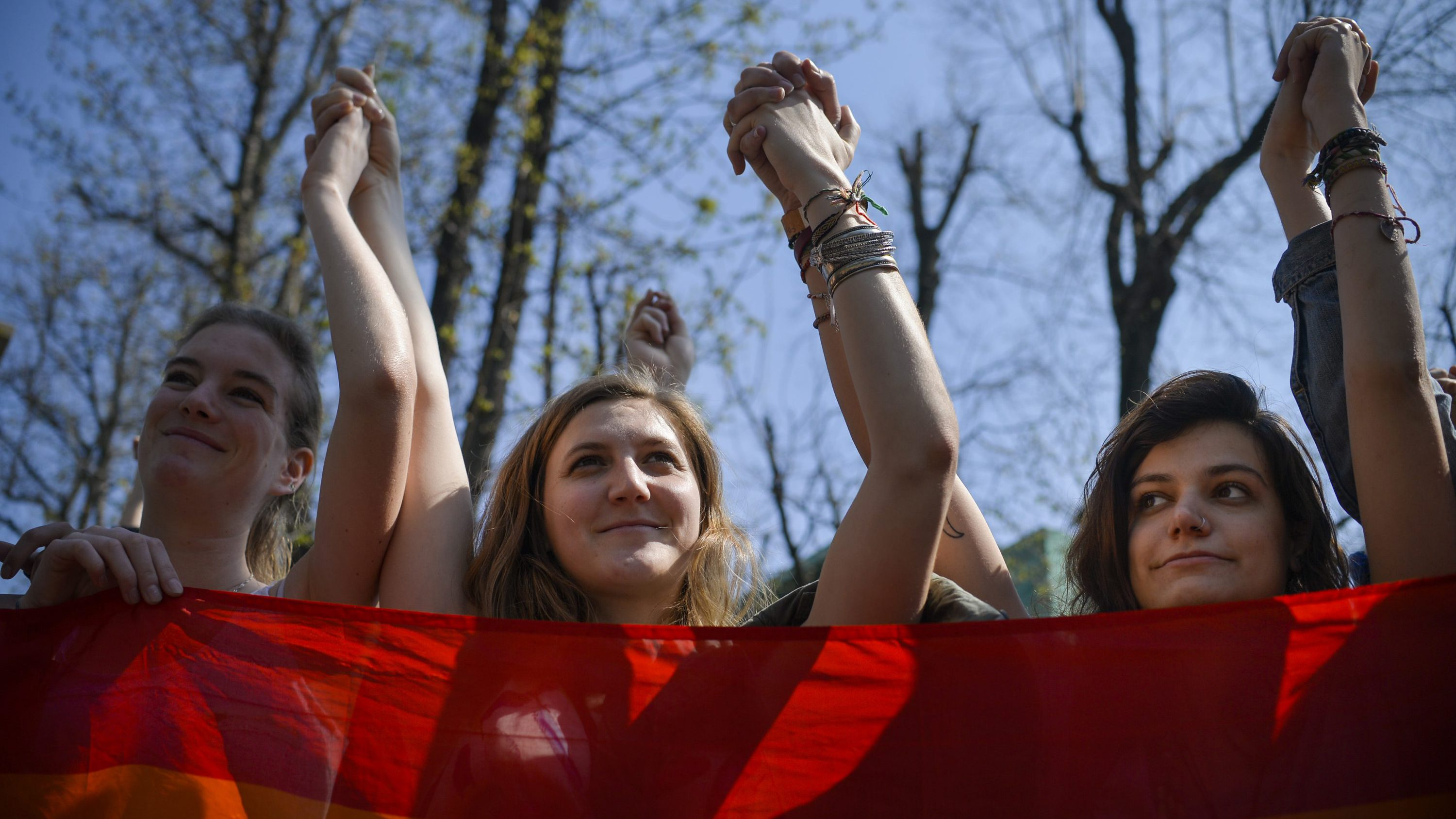 Women hold hands holding a rainbow flag during a protest against homophobia in Bucharest, Romania, Saturday, April 1, 2017. Ioan Denes, a Romanian senator claimed during a press conference that same sex couples don't have the right to hold hands on the street, as they infringe on his liberties.