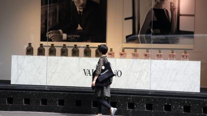 A Chinese tourist walks past a commercial outside the Galeries Lafayette general store in Paris, France, Wednesday, Aug. 26, 2015. The Shanghai stock market is dropping. Will the Chinese keep shopping? It's a huge question for Western luxury firms and for their brands such as Gucci, Chanel, Moet, Hennessy, Louis Vuitton and Burberry. (AP Photo/Francois Mori)