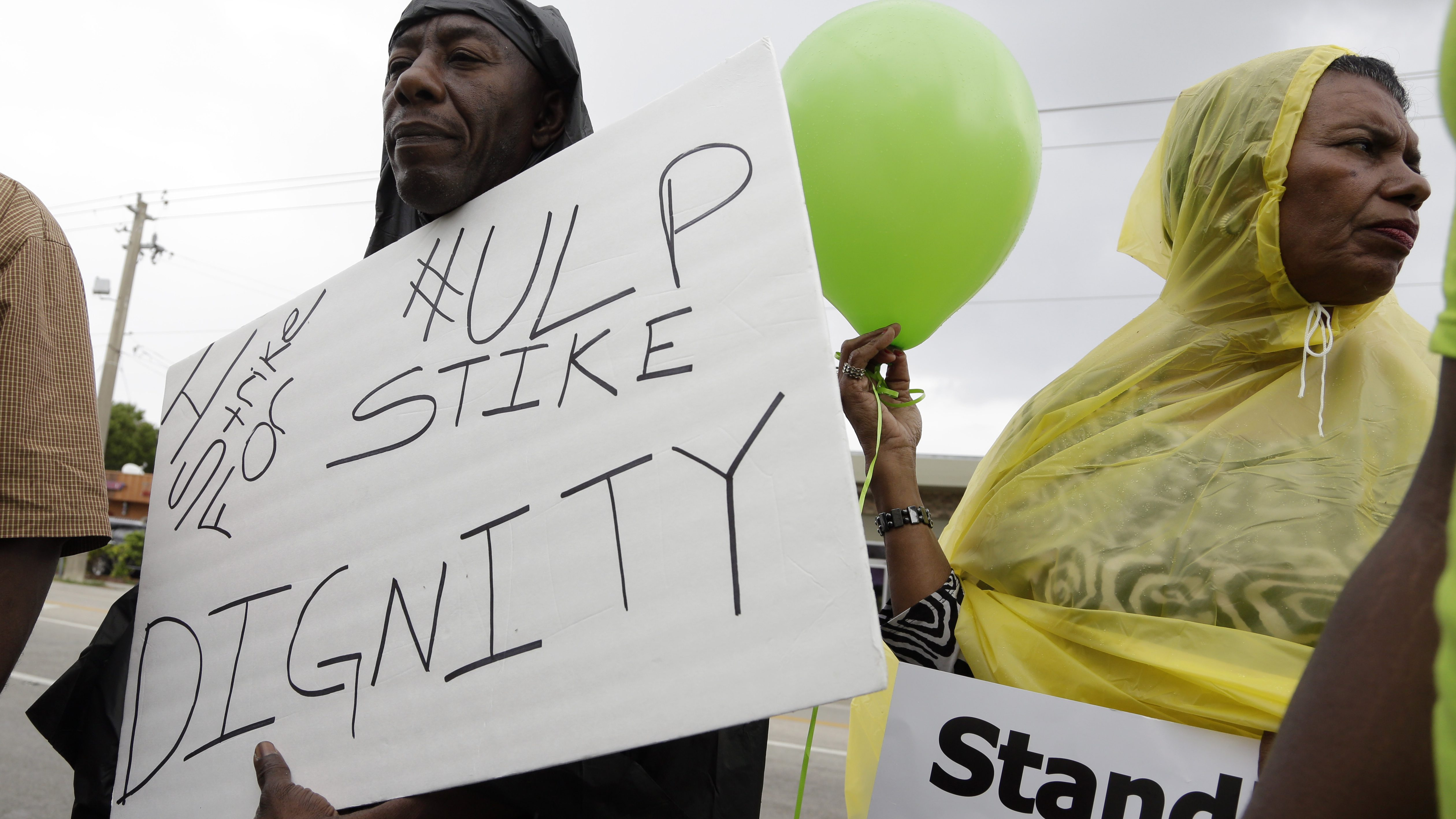 Striking Walmart employee Paul Toussaint, of Miami, left, and activist Juanita Alvarez, of Miami, right, march outside of Walmart, protesting the company's firings and disciplinary actions against employees who have gone on strike in the past, Wednesday, June 4, 2014, in North Miami Beach, Fla. This is part of the national organization OUR Walmart which seeks improve working conditions for Walmart employees. Walmart's annual shareholders meeting is Friday in Arkansas.