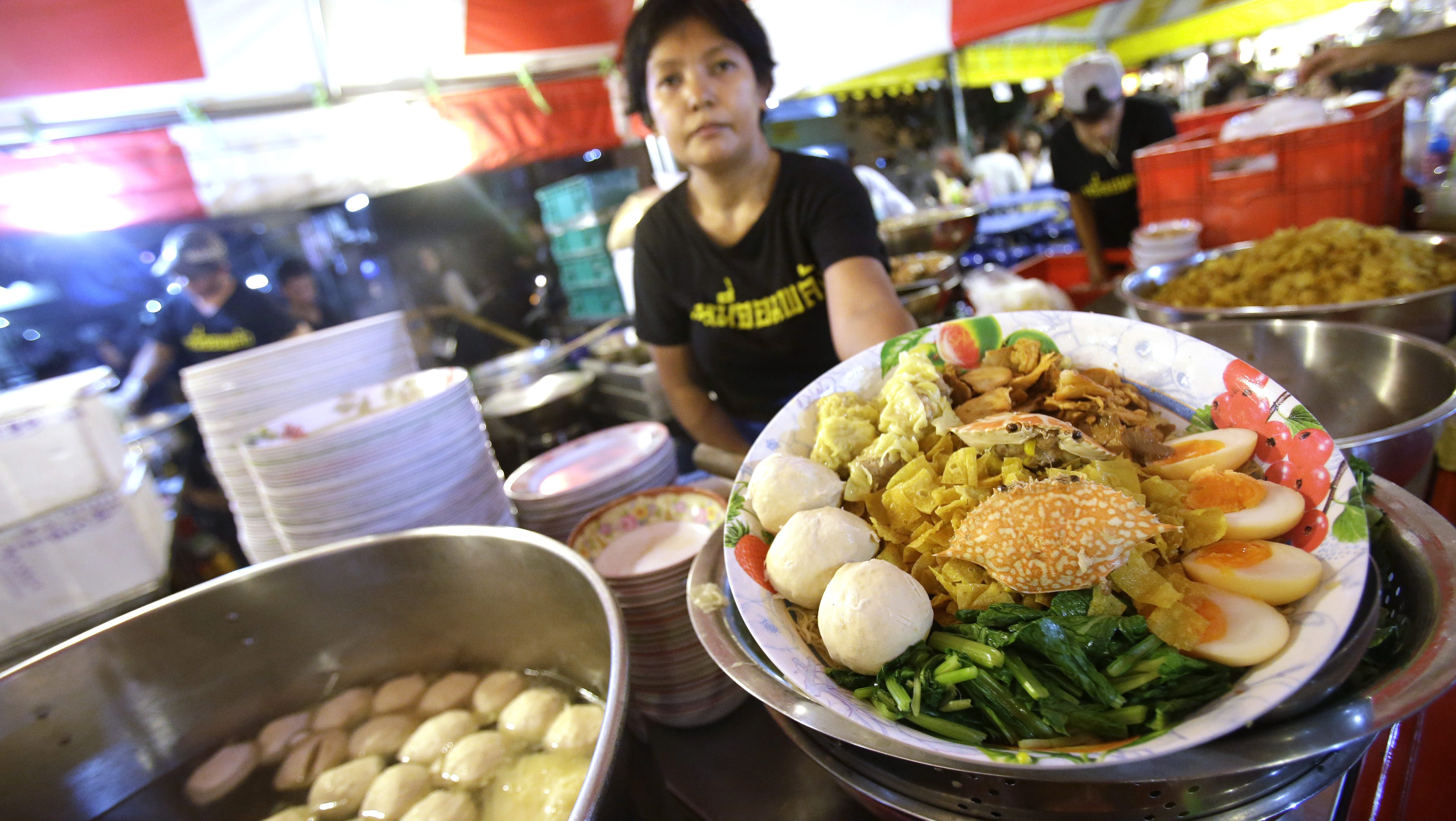 """In this Thursday, Oct. 22, 2015 photo, a street food vendor displays a bowl of Bamee Jom Palang, or """"Power Noodles"""", at one of the most crowded food stalls at Rotfai Market in Bangkok, Thailand. The vendor, whose specialty dish is the 12-inch long noodles, challenges buyers to finish eating the dish within five minutes. Those who can don't have to pay the 350 baht ($10) price.  In cities like Bangkok, street food remains the heart and soul of local cuisine, sold day and night from carts and makeshift stands. The classic Bangkok night market has evolved from catering mostly to club-goers looking for a late-night eat to offering real shopping opportunities for the city's large, young and relatively affluent middle class. (AP Photo/Sakchai Lalit)"""