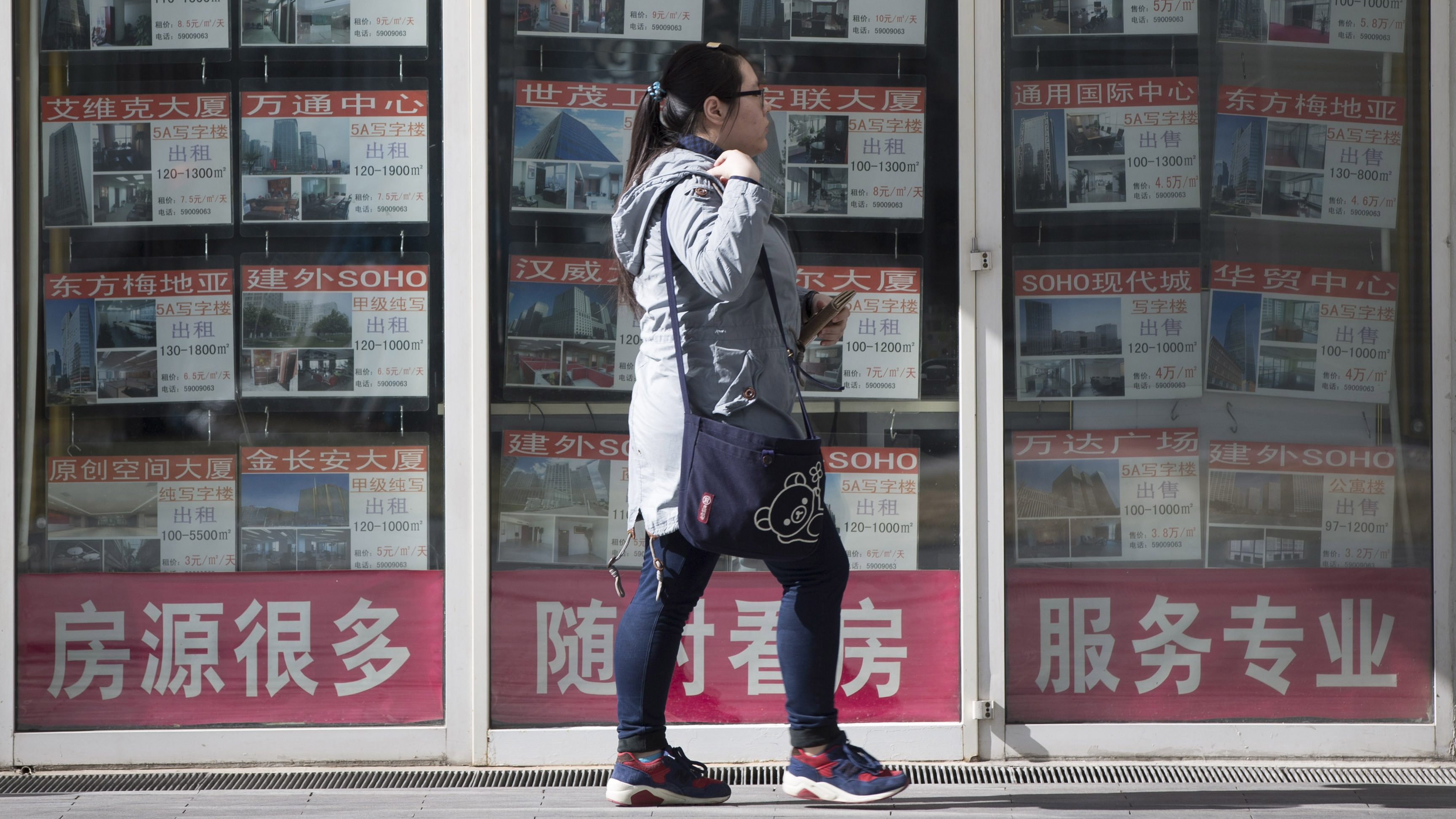 A Chinese woman walks in front of a real estate agent at center business district in Beijing