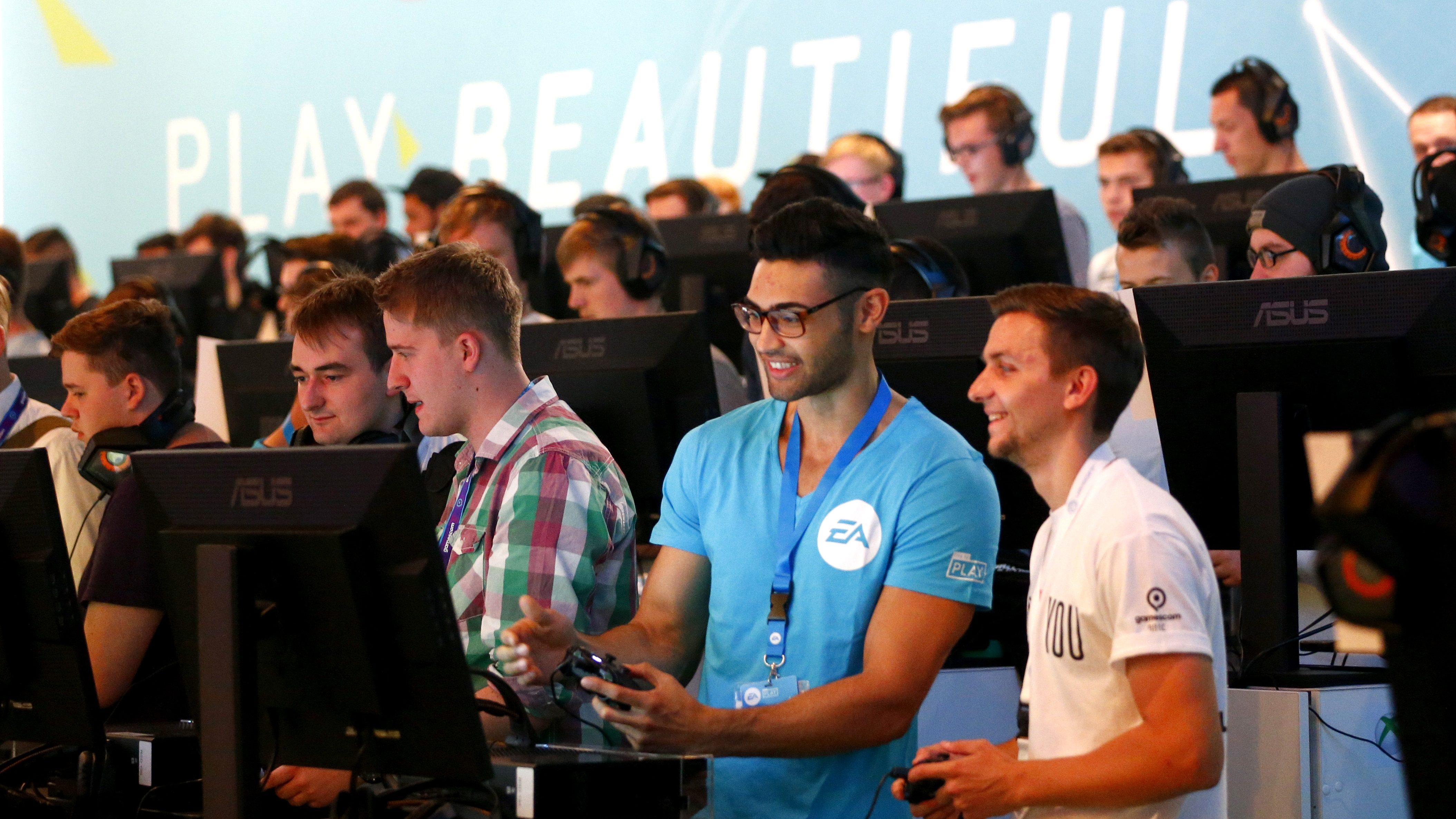 """Visitors play """"FIFA 16"""", published by EA Sports, using an Xbox One during the Gamescom fair in Cologne, Germany August 5, 2015. The Gamescom convention, Europe's largest video games trade fair, runs from August 5 to August 9."""