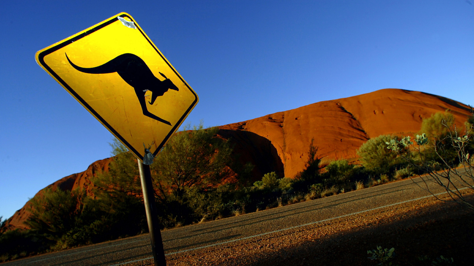 -PHOTO TAKEN 20APR04- A road sign near Uluru (Ayers Rock), about 350 kilometres (220 miles) south west of the central Australian town of [Alice Springs] warns drivers of the dangers of kangaroos crossing the road April 20, 2004. 40 years ago Uluru, which belongs to the Anangu Aboriginal people, was visited by around 1,000 tourists annually. Since then it has become one of Australia's major tourist destinations, attracting 400,000 visitors every year. - RTXMK0L