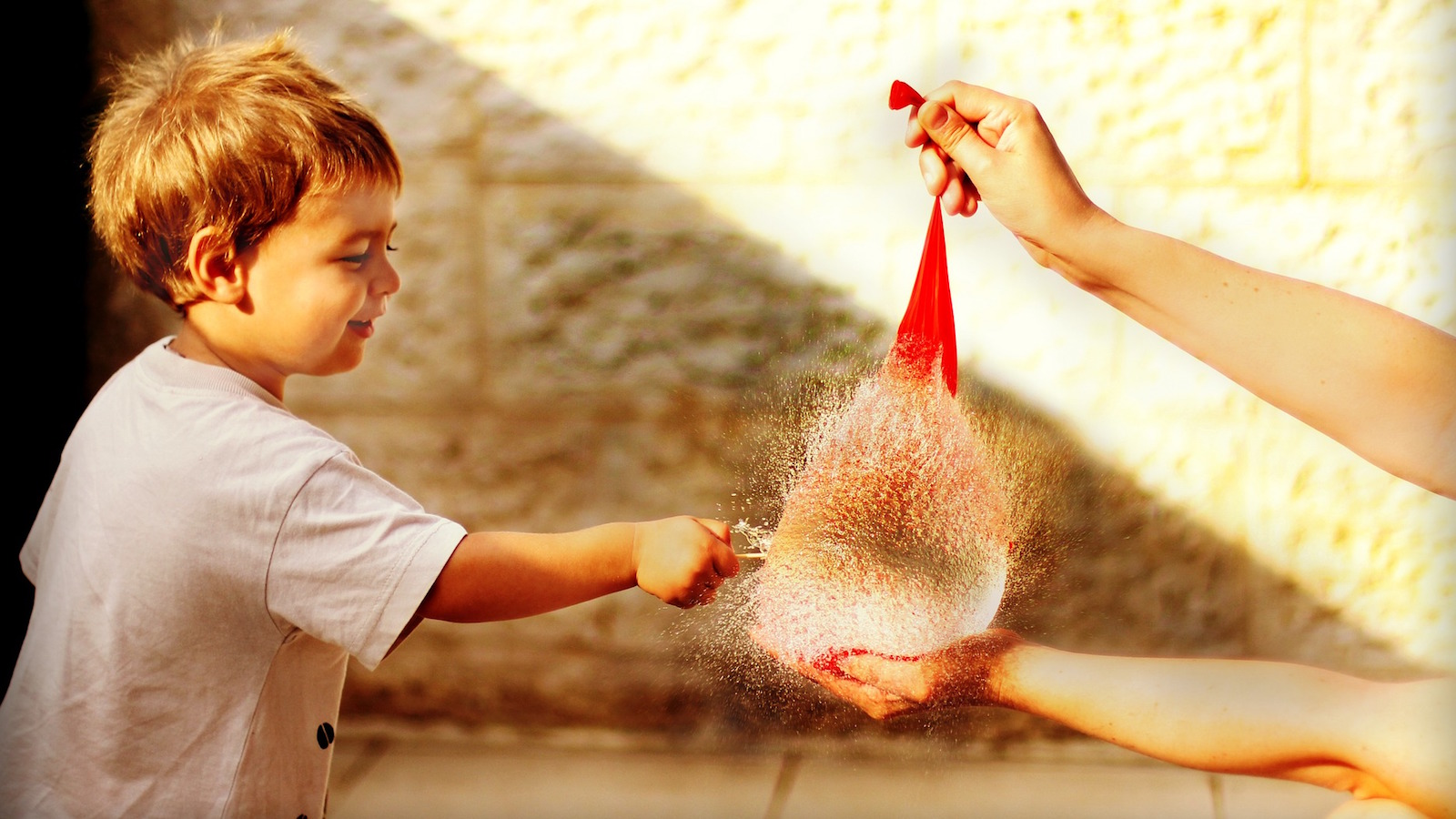 child about to pop water balloon
