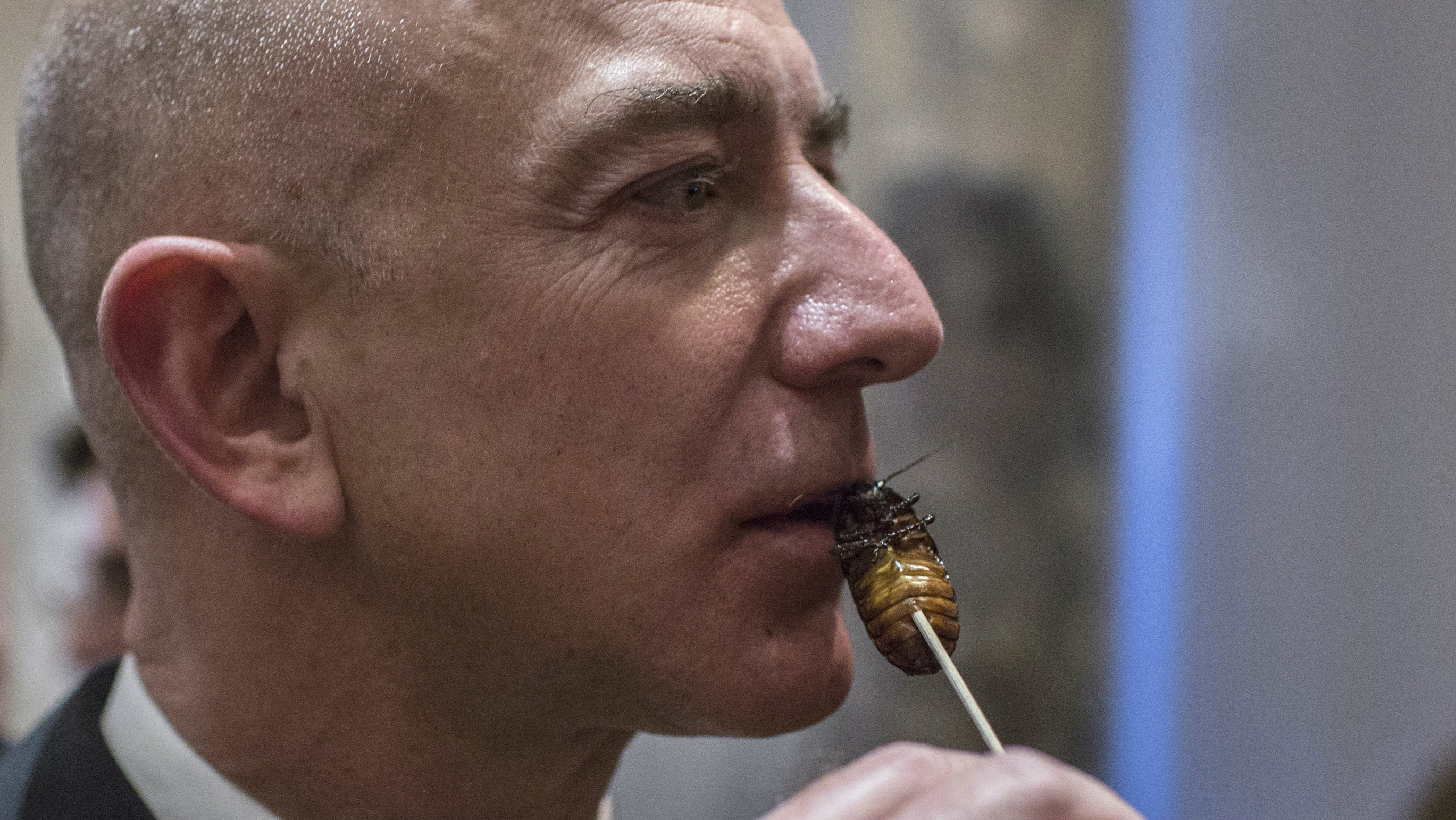 bezos with a cockroach lollipop