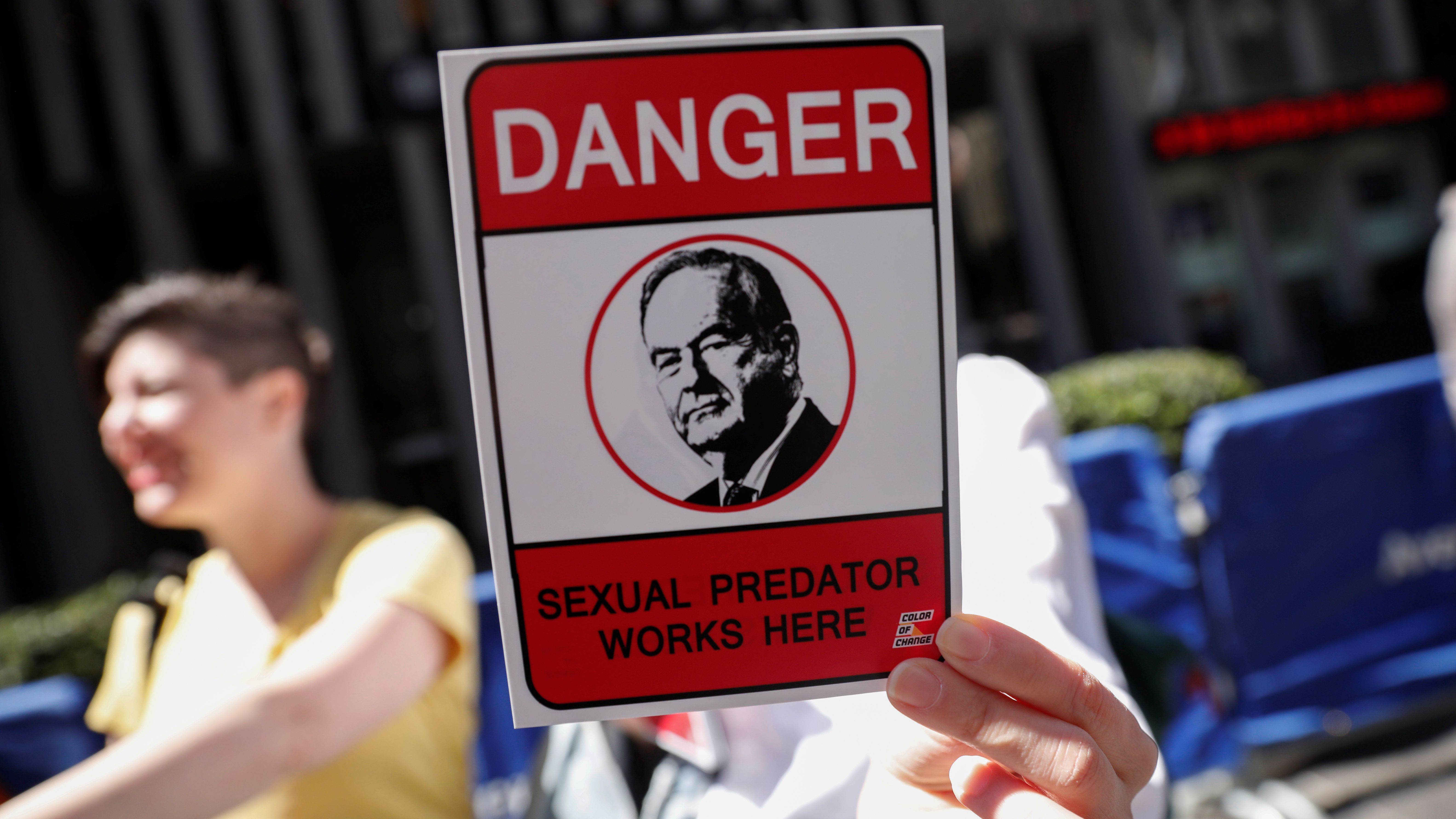 A demonstrator holds a sign at a protest calling for the firing of Fox News Channel TV anchor Bill O'Reilly outside the News Corporation headquarters in New York City, New York, U.S., April 18, 2017.