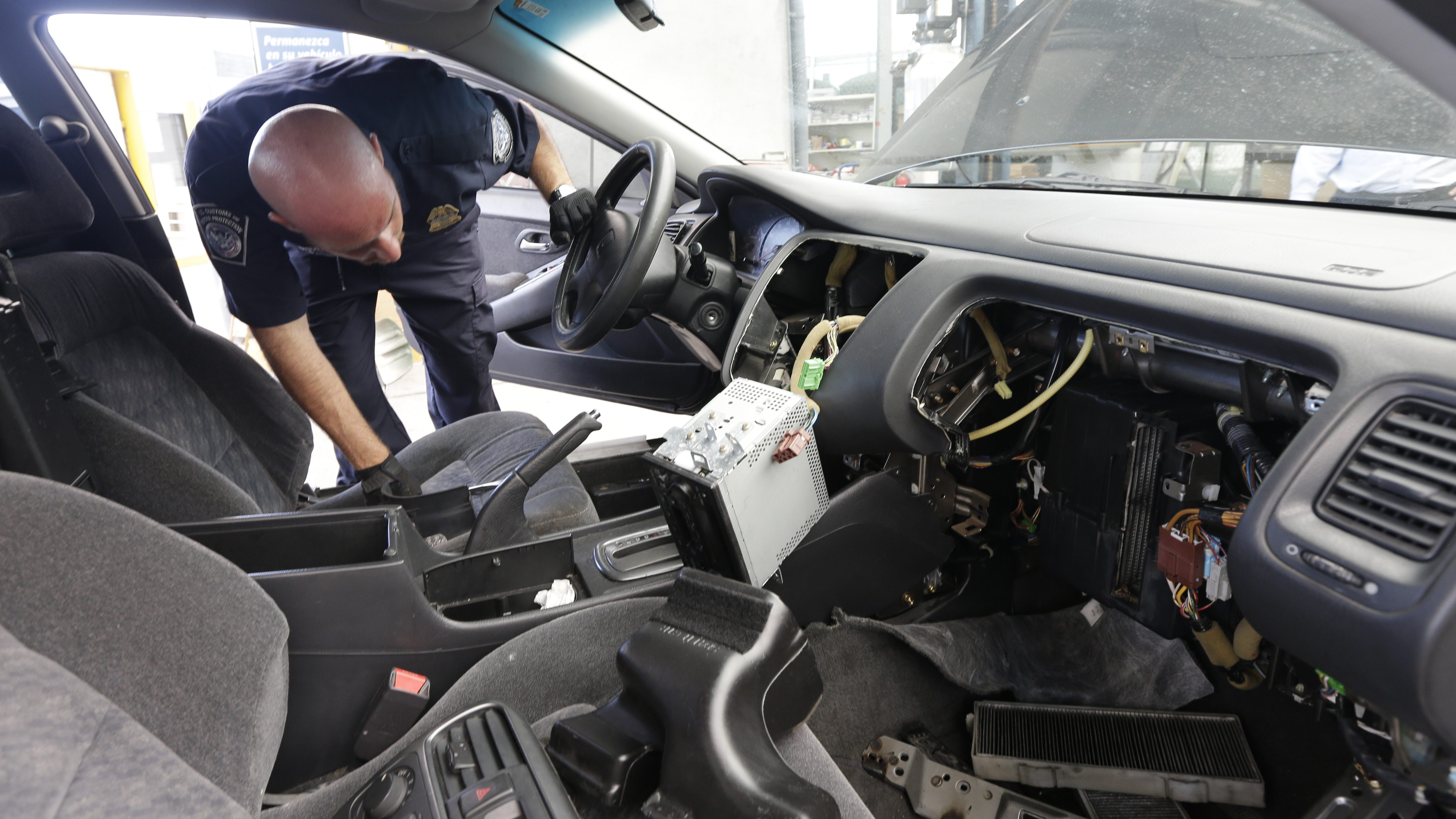A Customs and Border Protection officer looks in the dismembered dashboard of a Honda Accord