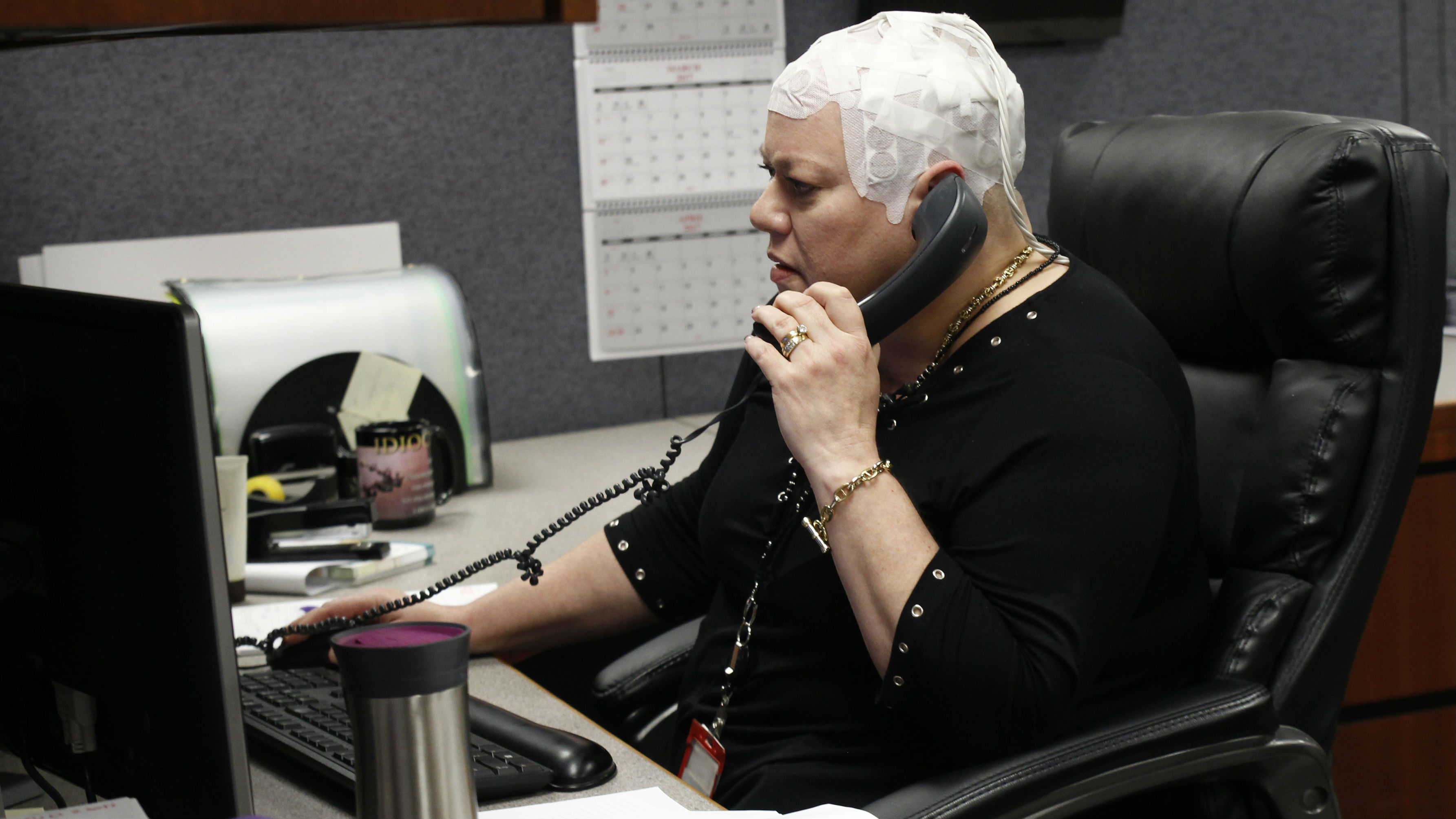 A patient wearing the Optune therapy device makes a phone call while at an office.