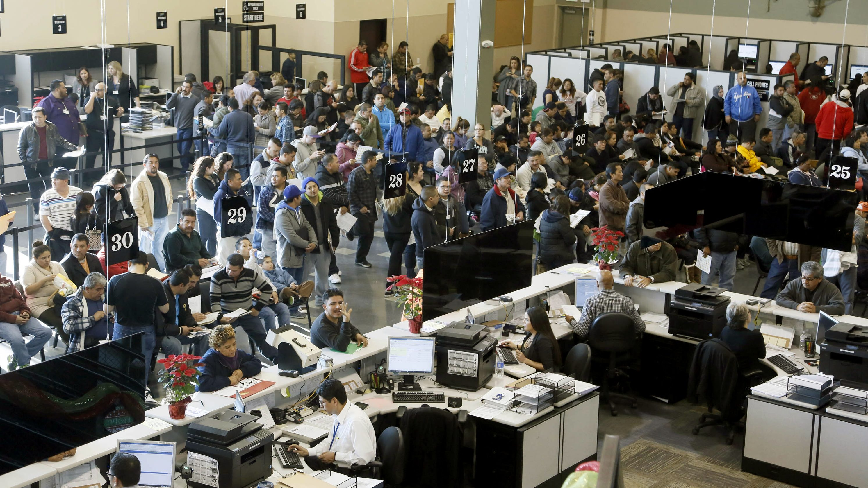 Immigrants line up at a California Department of Motor Vehicles office to register for drivers licenses