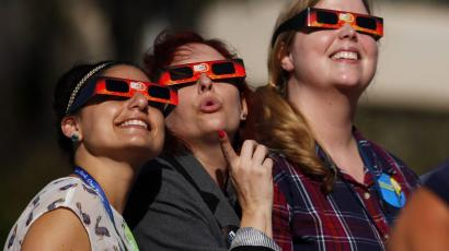 Women gaze up to view a partial solar eclipse outside the Reuben H. Fleet Science Center in San Diego, California.