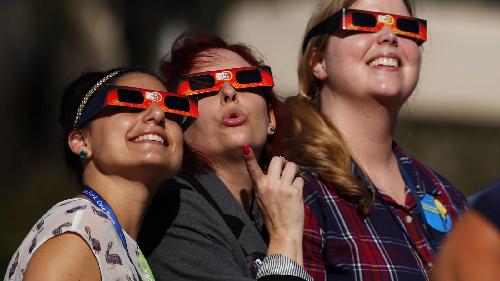 Women gaze up to view a partial solar eclipse outside the Reuben H. Fleet Science Center in San Diego, California October 23, 2014.    REUTERS/Mike Blake (UNITED STATES - Tags: ENVIRONMENT SOCIETY) - RTR4BE48