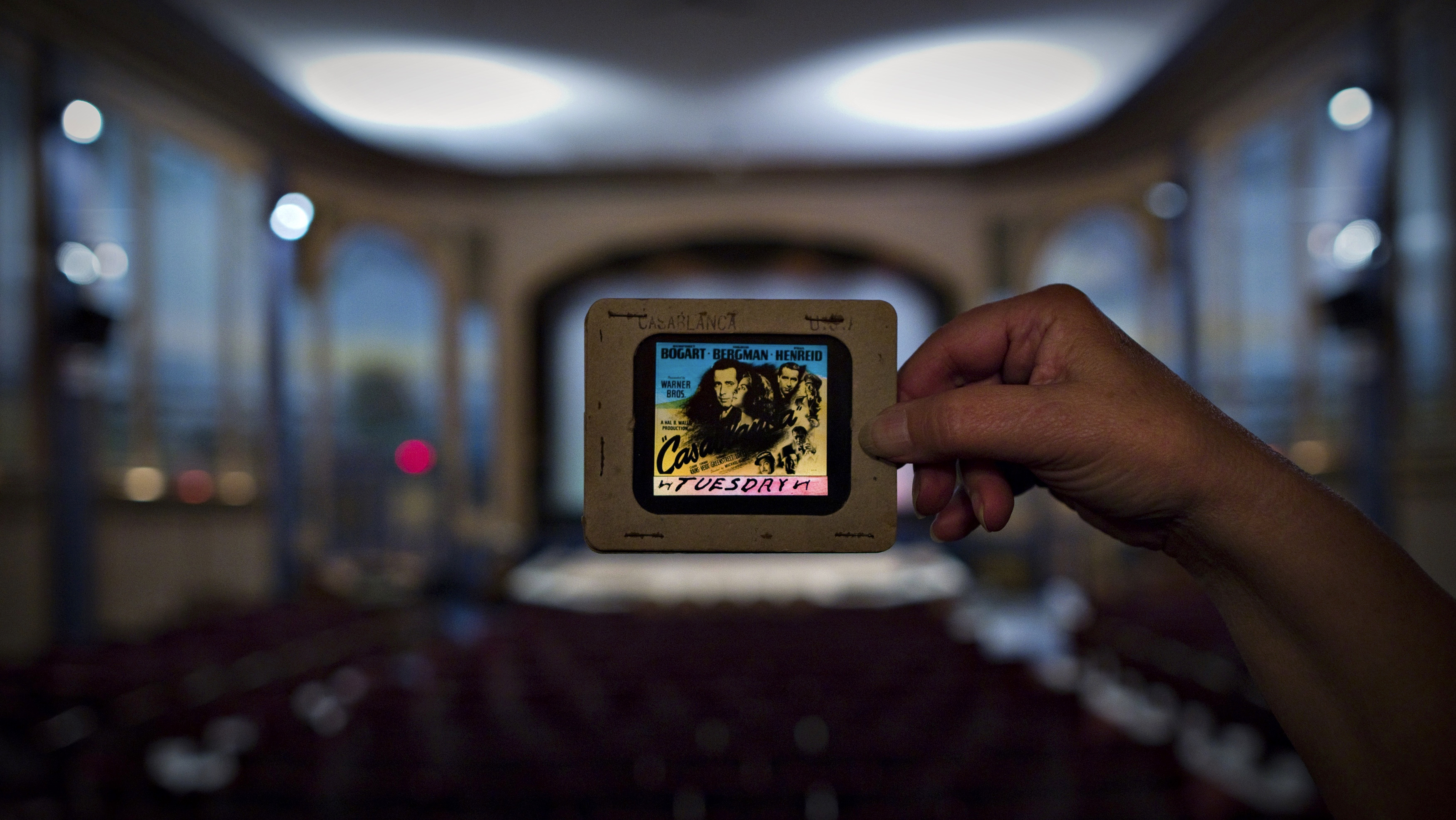 Cinema owner Ann Nelson holds up an original slide from the movie Casablanca inside The Patricia Theatre in Powell River, British Columbia October 31, 2013. The Patricia was founded in 1913 and entertained customers with silent movies, vaudeville shows and even local boxing matches. The venue has been running continuously since it opened, and still hosts a wide variety of entertainment, from cinema to concerts and vaudeville. The Patricia was the first cinema built in Powell River and although others opened up there, none have survived, meaning that the Patricia is both the town's first and last movie theatre. Picture taken October 31, 2013. REUTERS/Andy Clark    (CANADA - Tags: ENTERTAINMENT SOCIETY)  ATTENTION EDITORS: PICTURE 09 OF 28 FOR PACKAGE 'THE FIRST AND LAST MOVIE THEATRE'  TO FIND ALL IMAGES SEARCH 'PATRICIA CLARK' - RTX15TI8